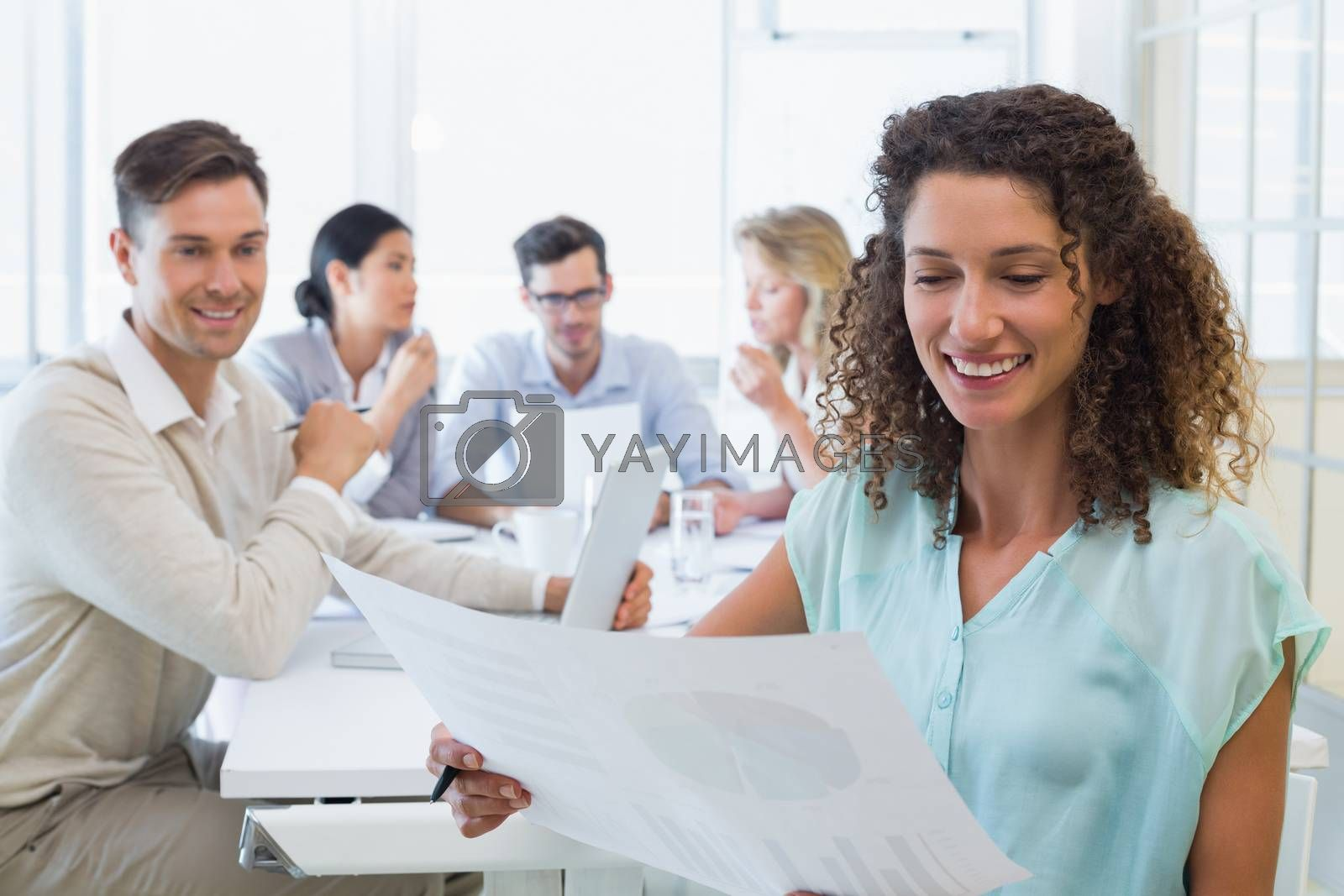 Royalty free image of Casual businesswoman reading document during meeting by Wavebreakmedia
