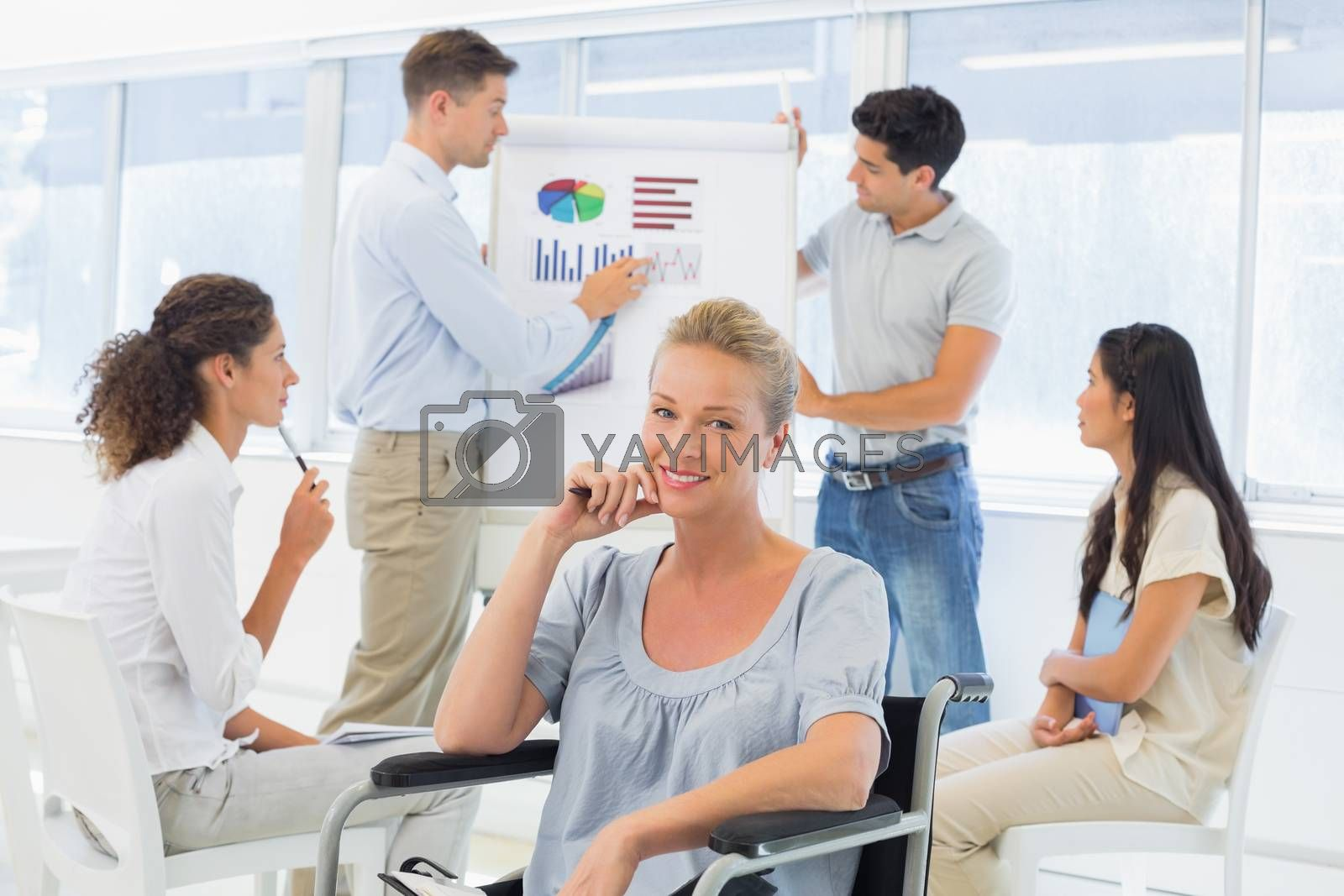 Royalty free image of Casual businesswoman in wheelchair smiling at camera during presentation by Wavebreakmedia