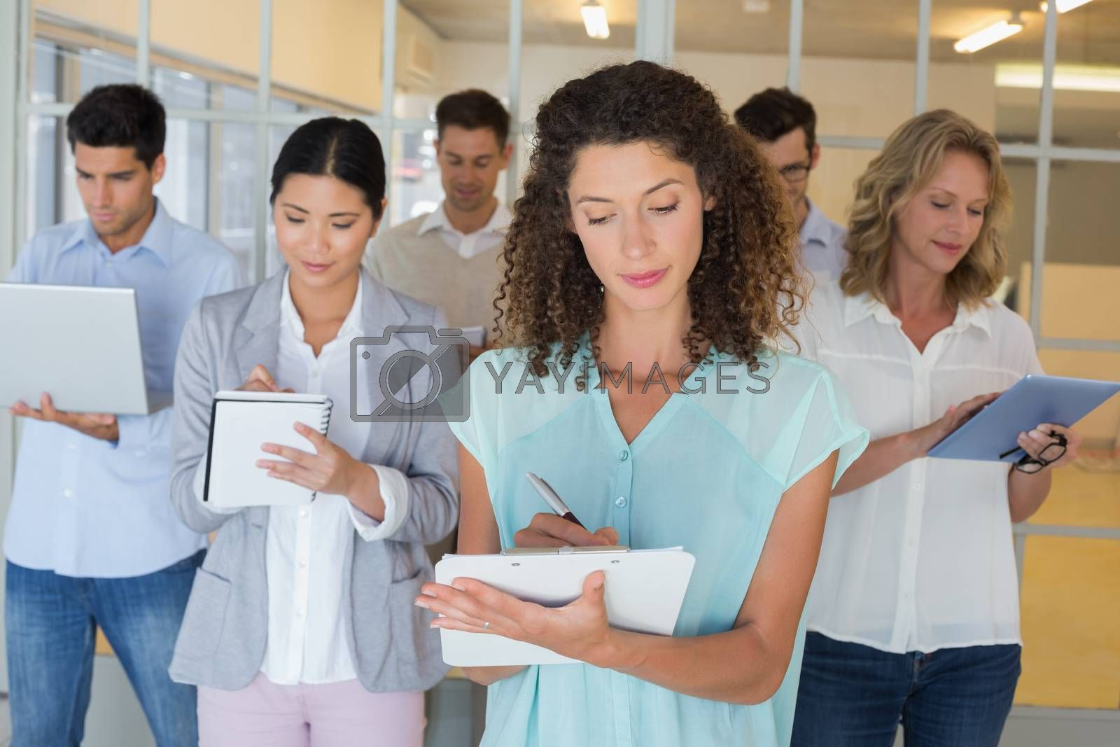 Royalty free image of Casual boss standing in front of her team all taking notes by Wavebreakmedia