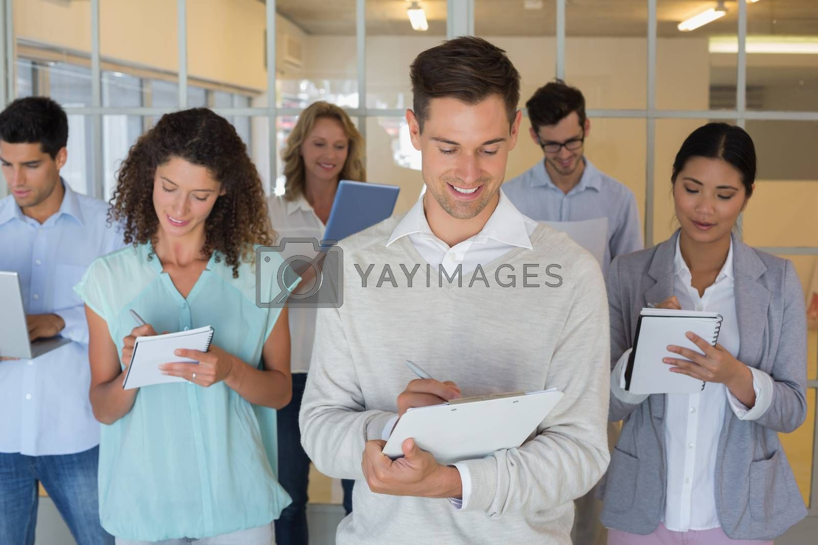 Royalty free image of Casual boss standing in front of his team all taking notes by Wavebreakmedia