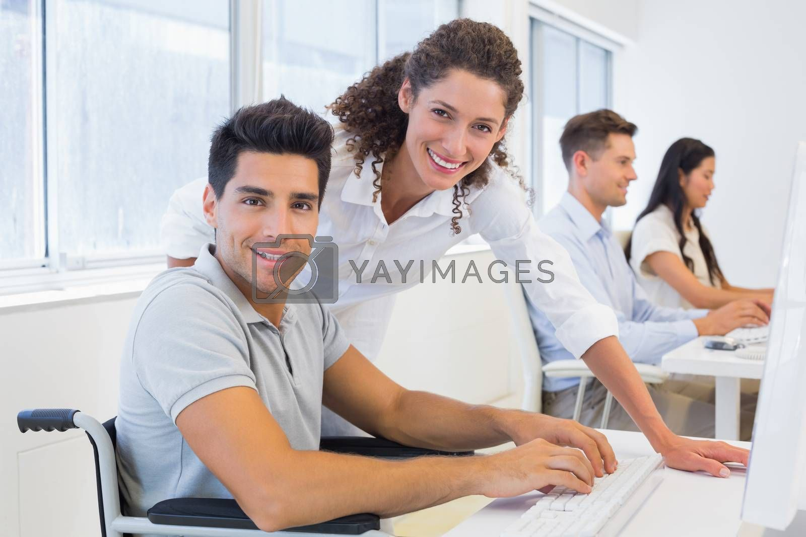 Royalty free image of Casual businessman in wheelchair working at his desk with colleague by Wavebreakmedia