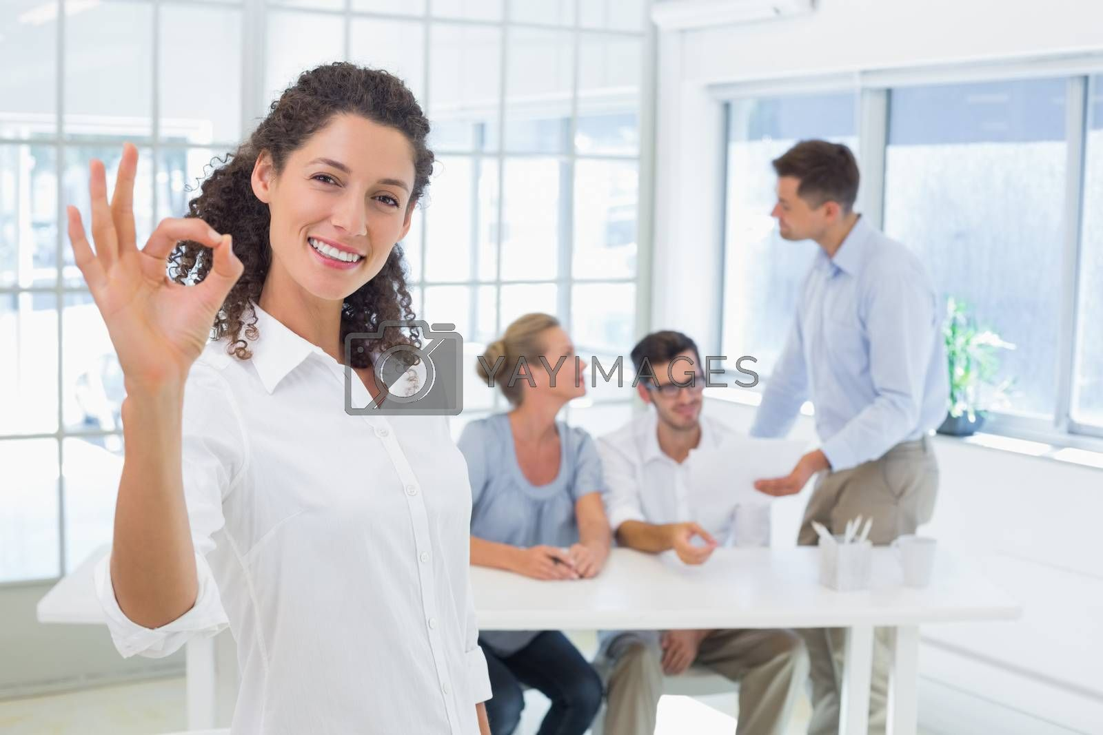 Royalty free image of Casual happy businesswoman making ok sign to camera by Wavebreakmedia