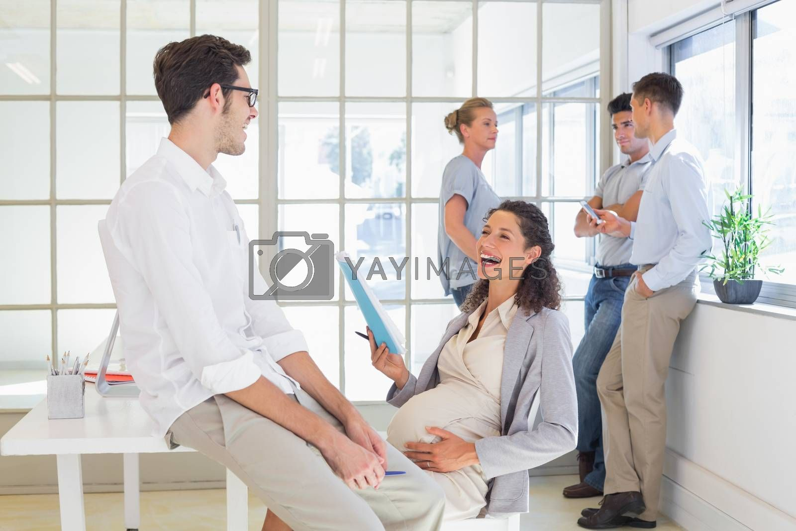 Royalty free image of Pregnant businesswoman laughing with colleague by Wavebreakmedia