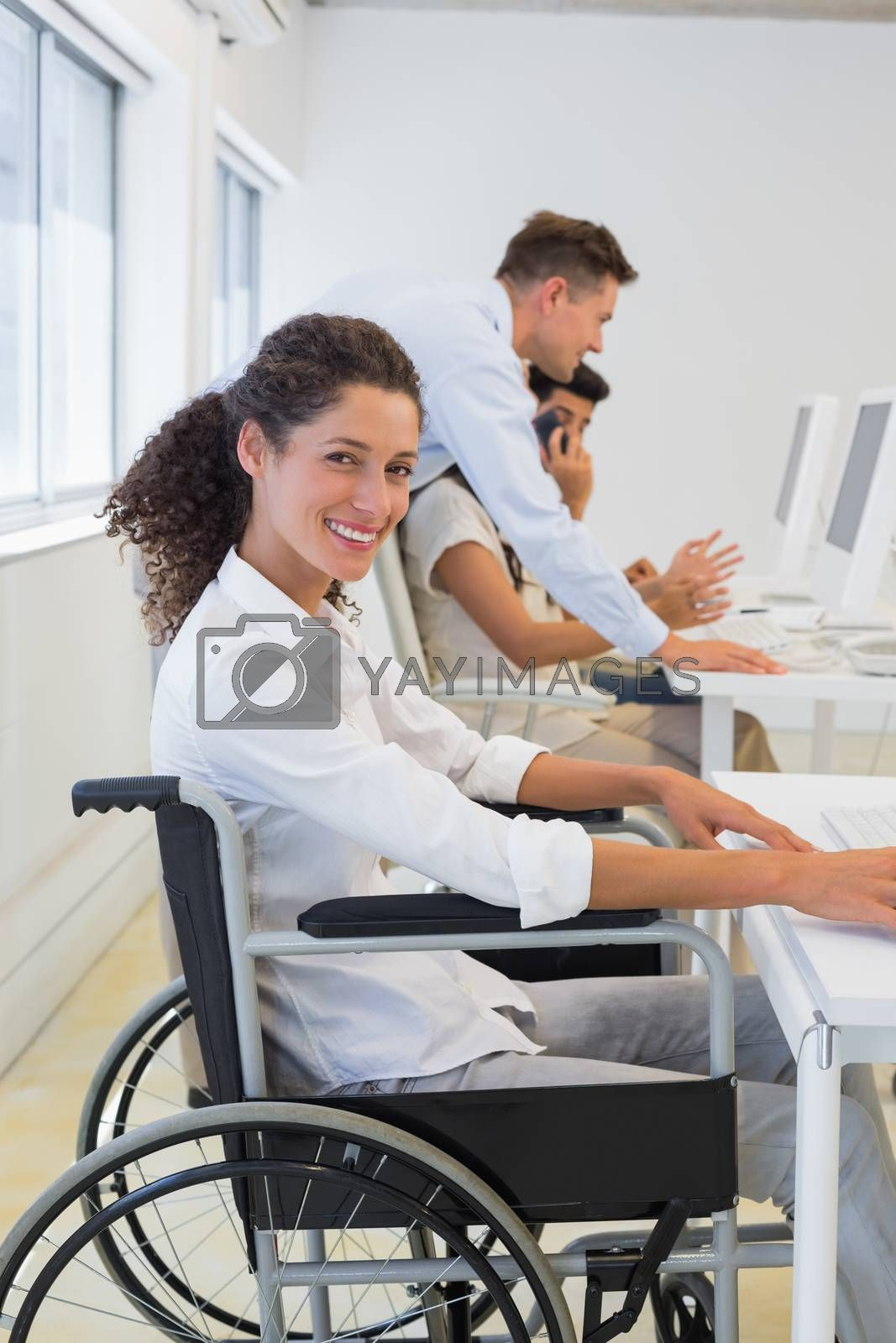 Royalty free image of Casual businesswoman in wheelchair working at her desk by Wavebreakmedia