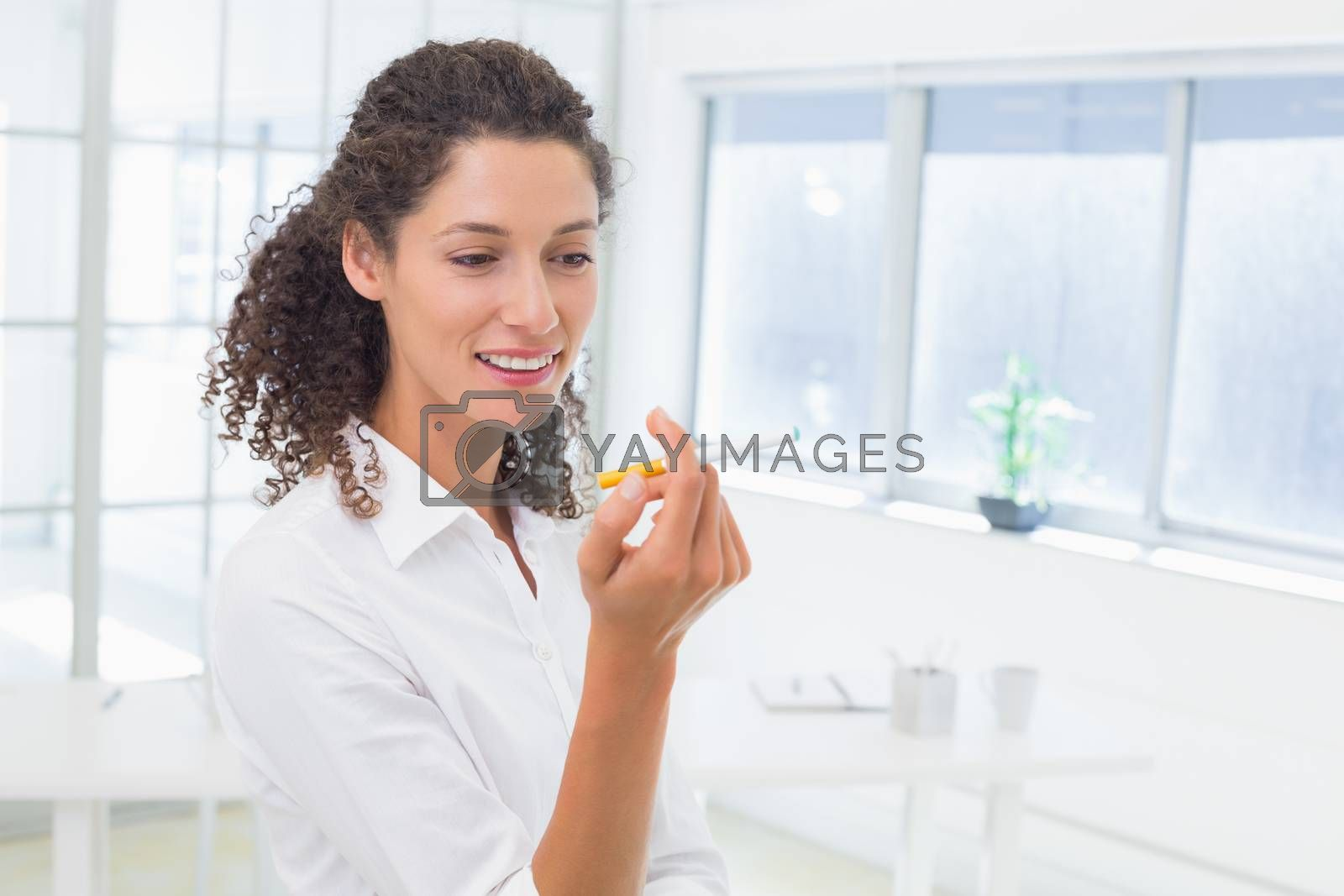 Royalty free image of Casual businesswoman looking at her electronic cigarette by Wavebreakmedia