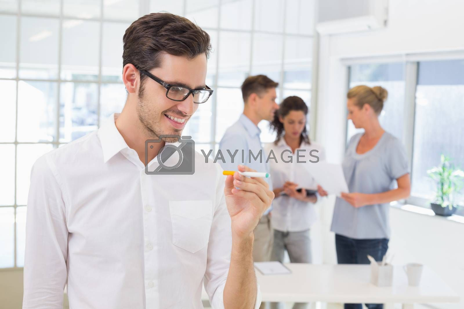 Royalty free image of Casual businessman smiling at his electronic cigarette by Wavebreakmedia