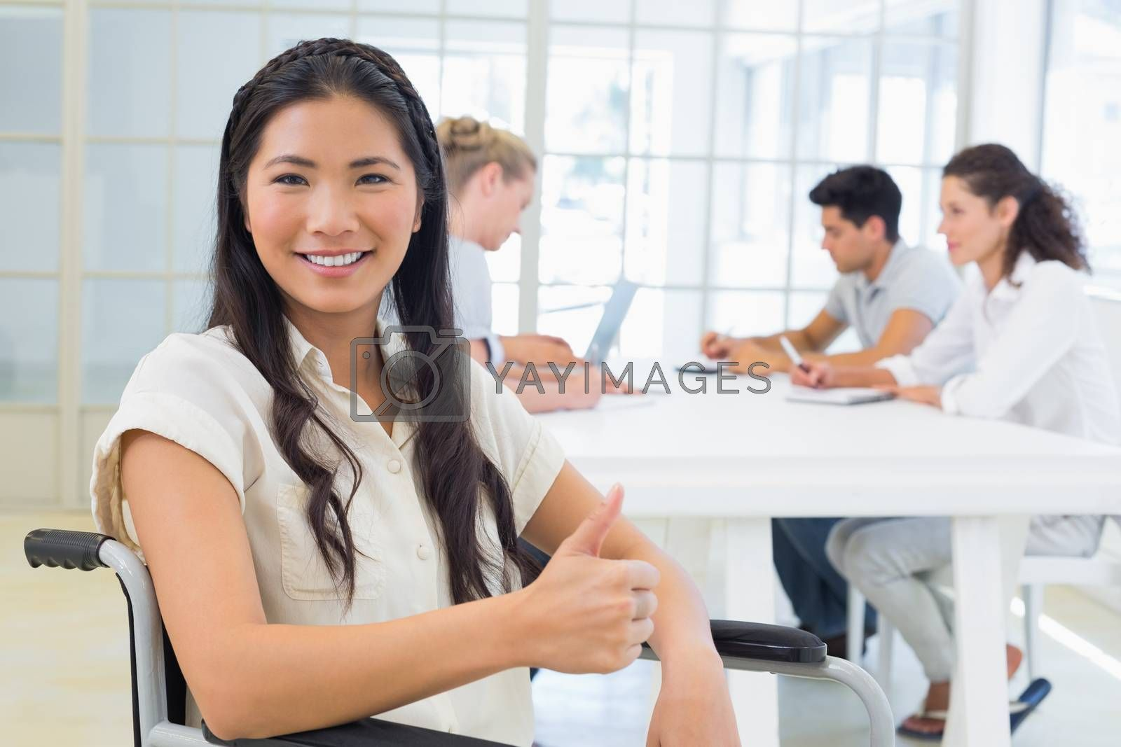 Royalty free image of Casual businesswoman in wheelchair smiling at camera giving thumbs up by Wavebreakmedia