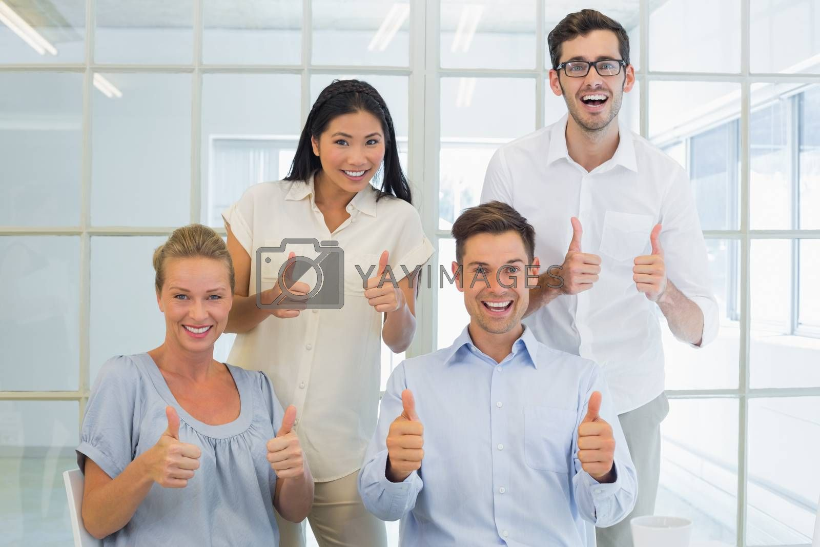 Royalty free image of Casual business team showing thumbs up to camera by Wavebreakmedia