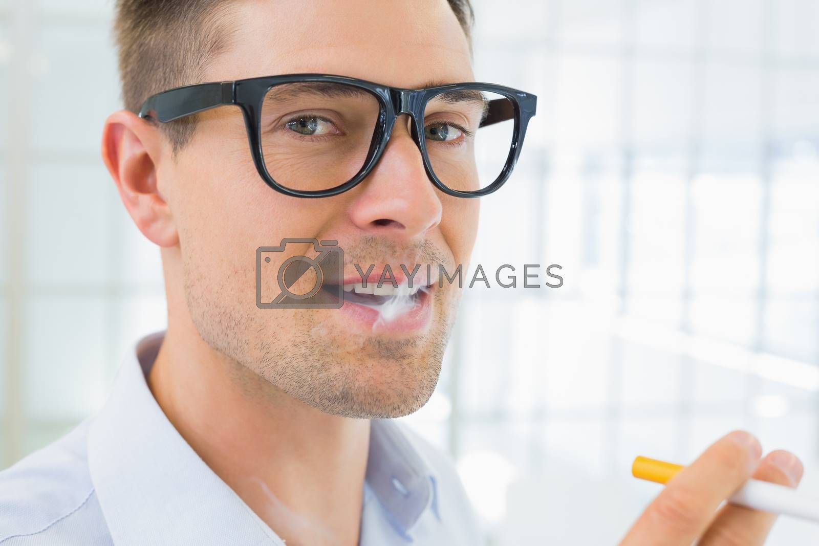 Royalty free image of Casual businessman smoking an electronic cigarette by Wavebreakmedia