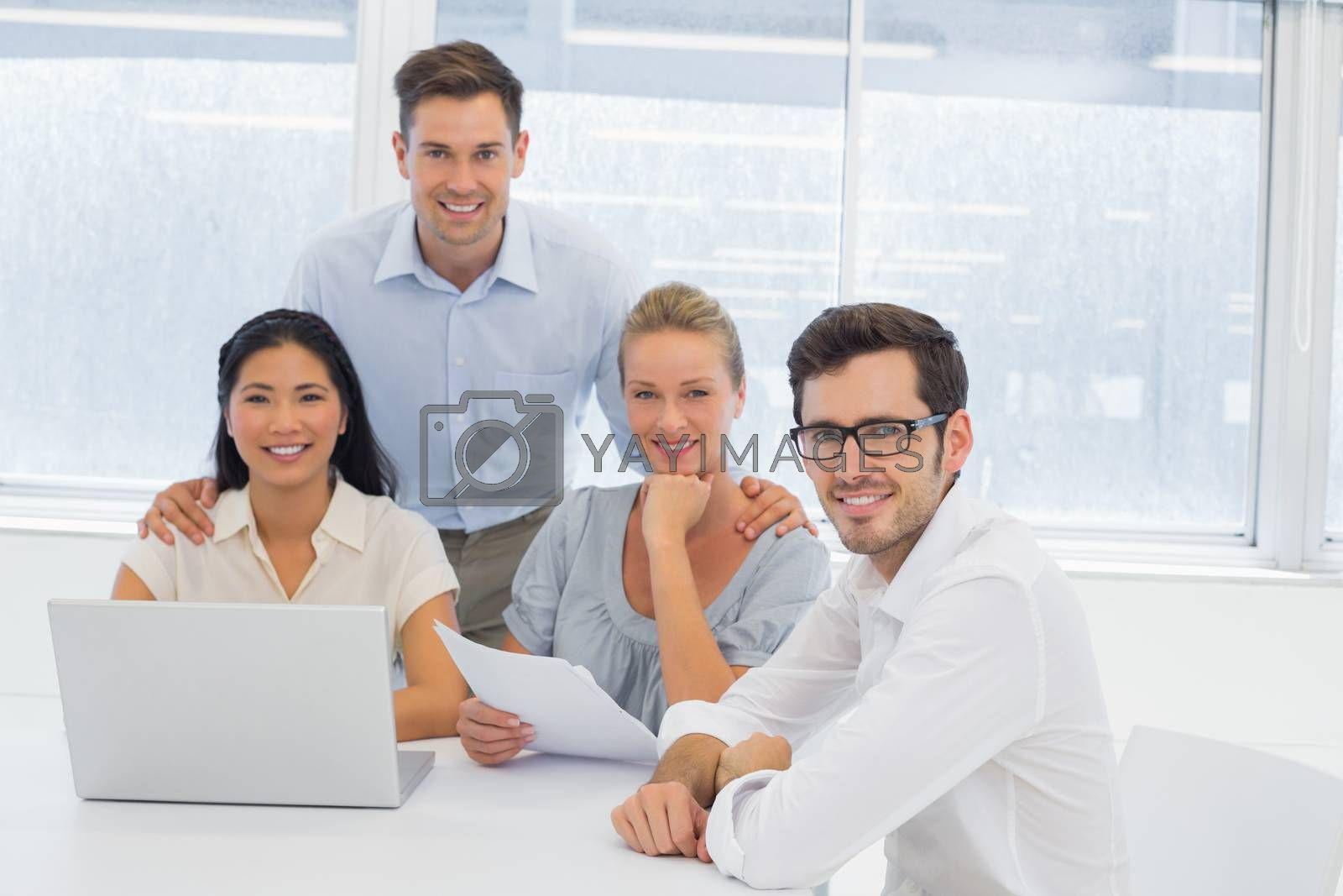 Royalty free image of Casual business team working together at desk smiling at camera by Wavebreakmedia