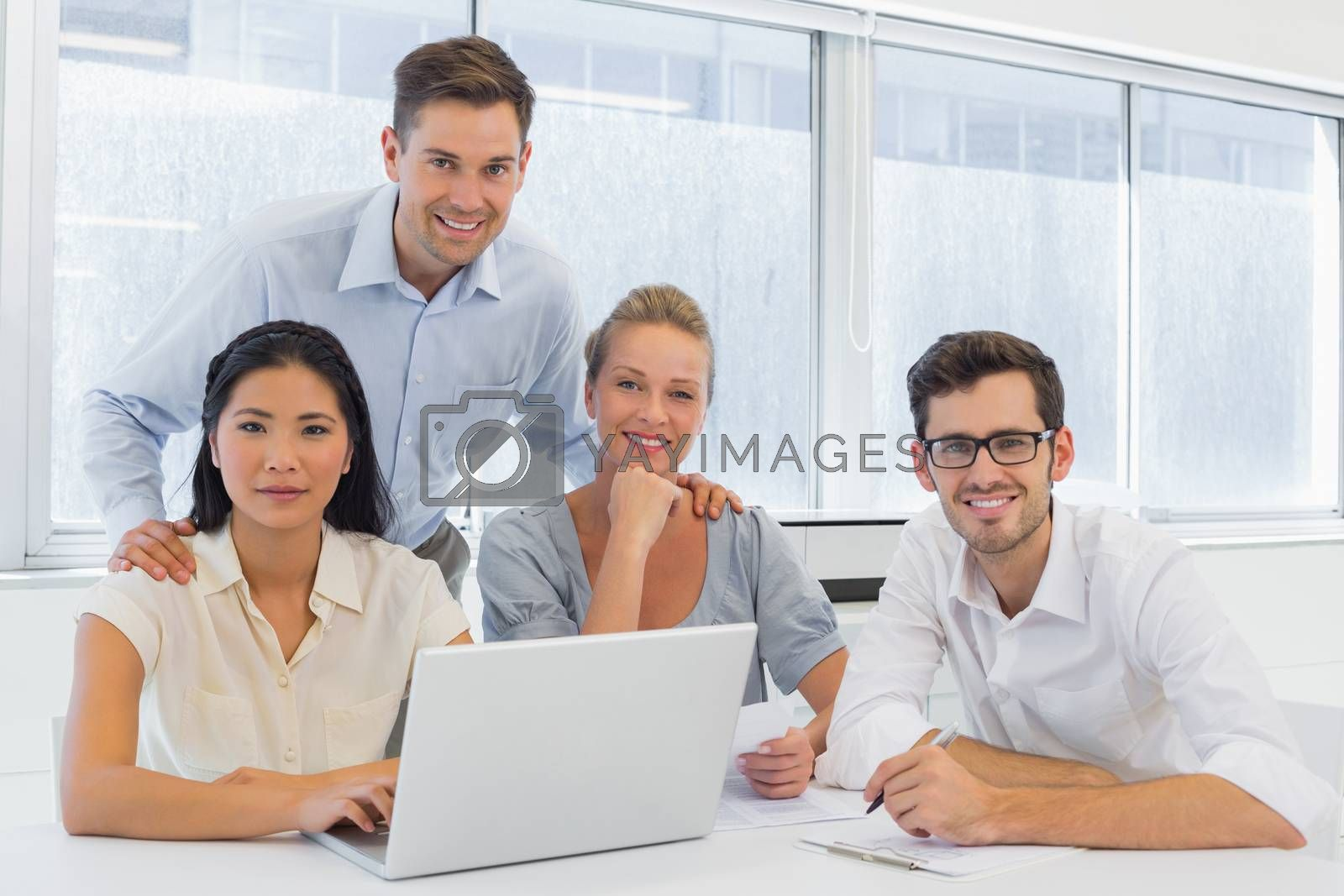 Royalty free image of Casual business team working together at desk using laptop by Wavebreakmedia