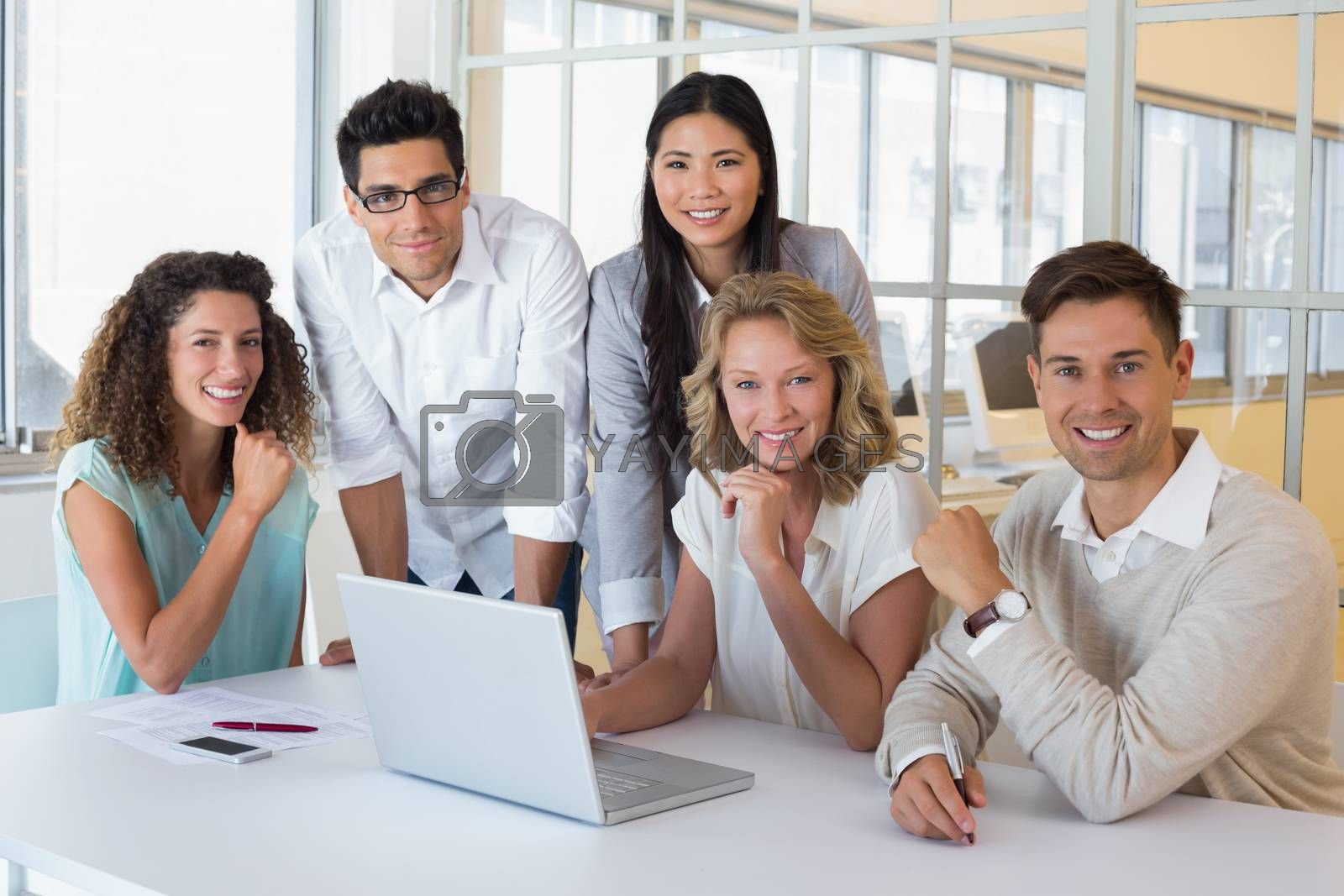 Royalty free image of Casual smiling business team having a meeting using laptop by Wavebreakmedia
