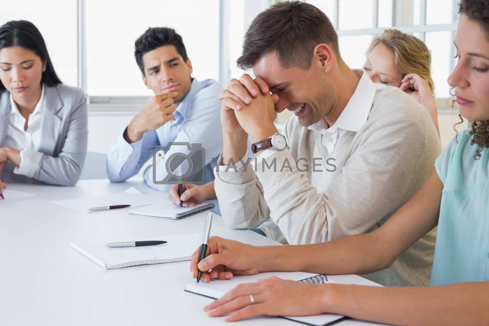 Royalty free image of Casual businessman trying not to laugh during meeting by Wavebreakmedia