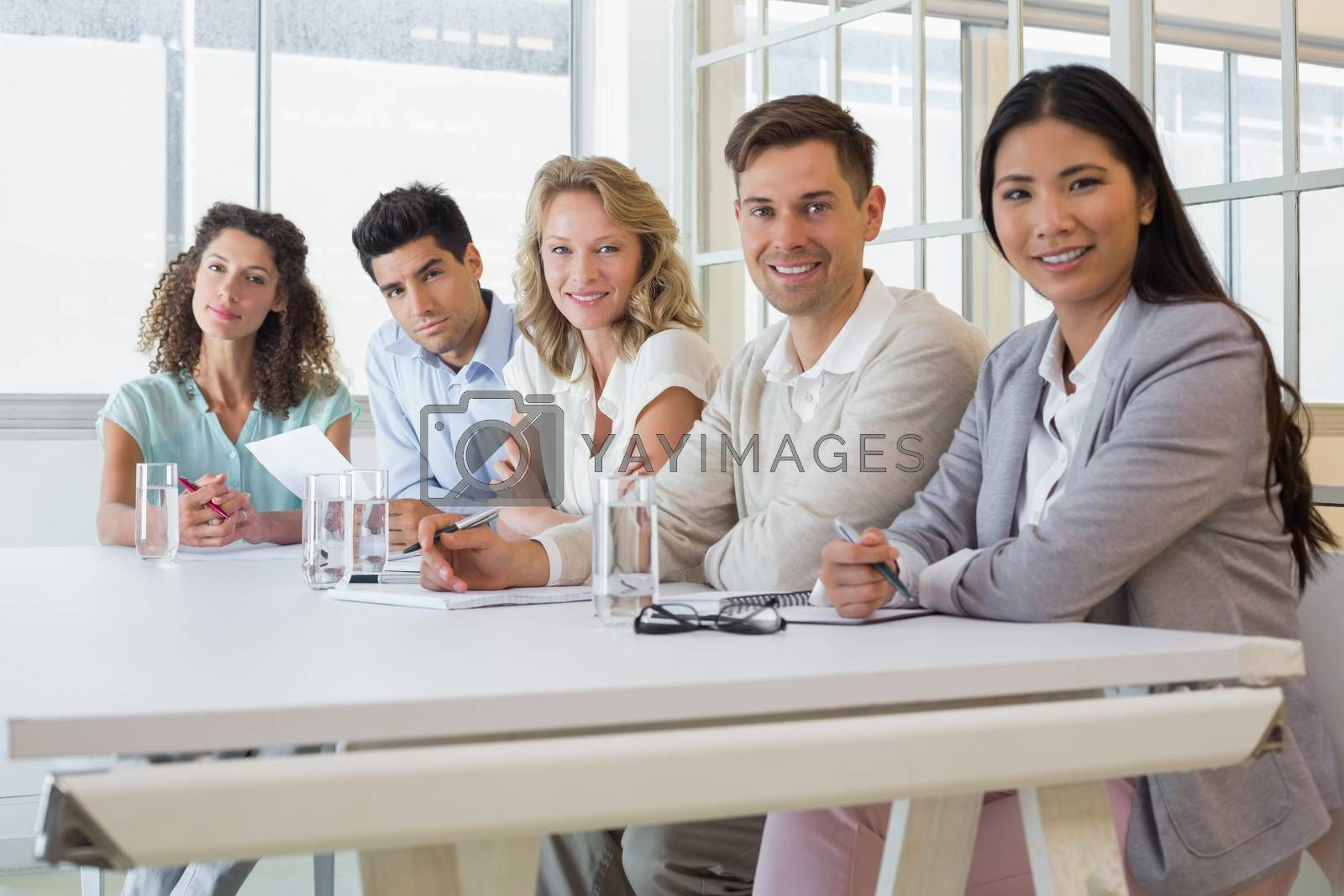Royalty free image of Casual business team smiling at camera during meeting by Wavebreakmedia