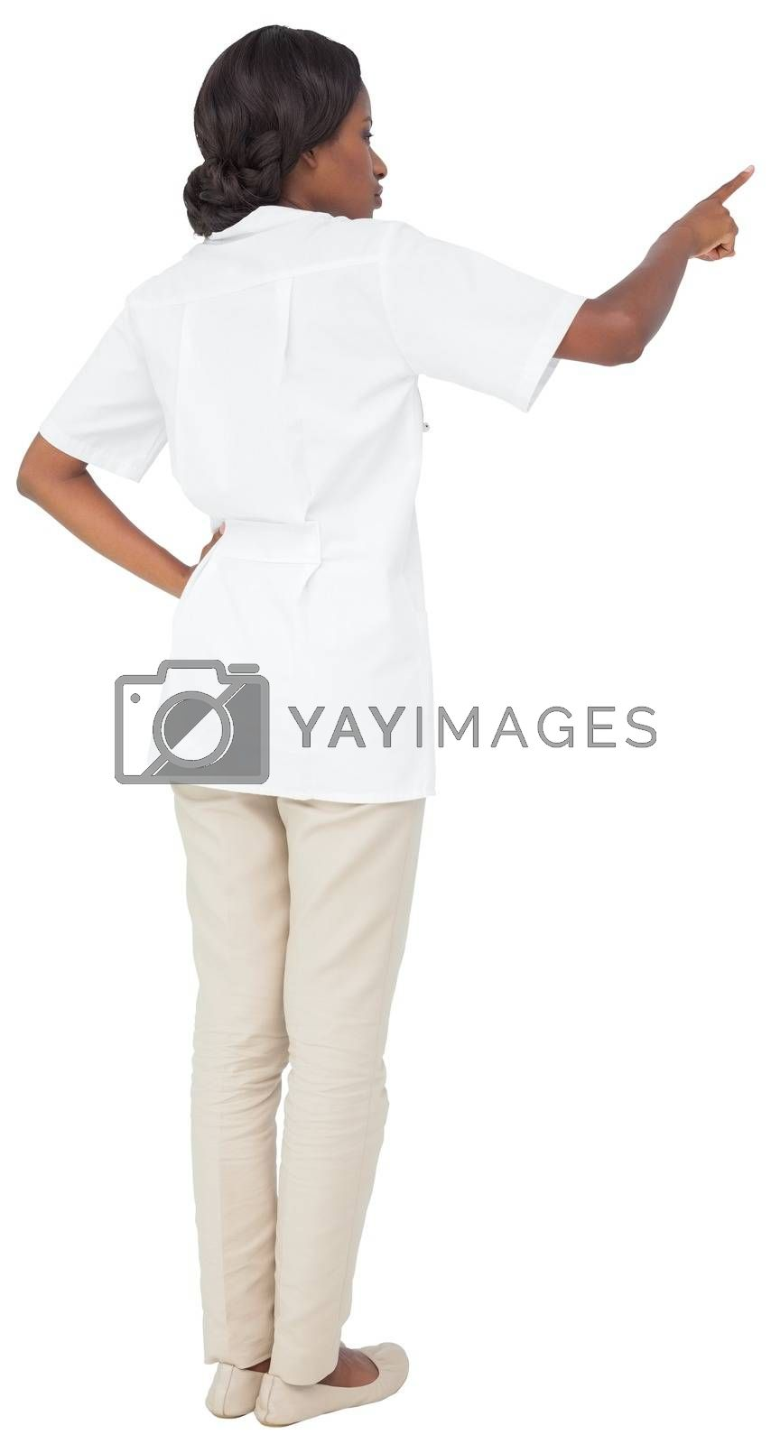 Royalty free image of Young nurse in tunic pointing by Wavebreakmedia