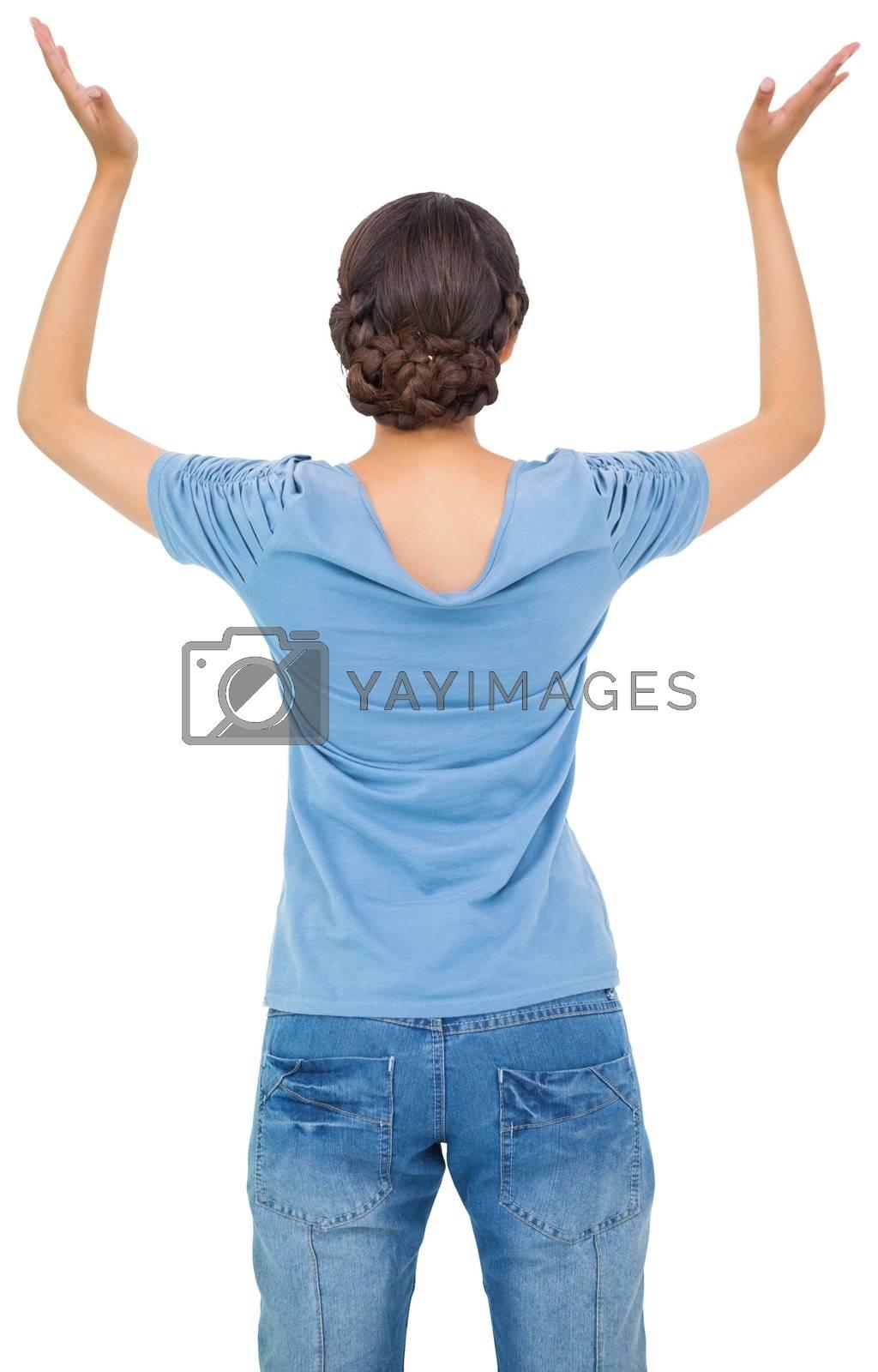 Royalty free image of Brunette woman in jeans gesturing by Wavebreakmedia