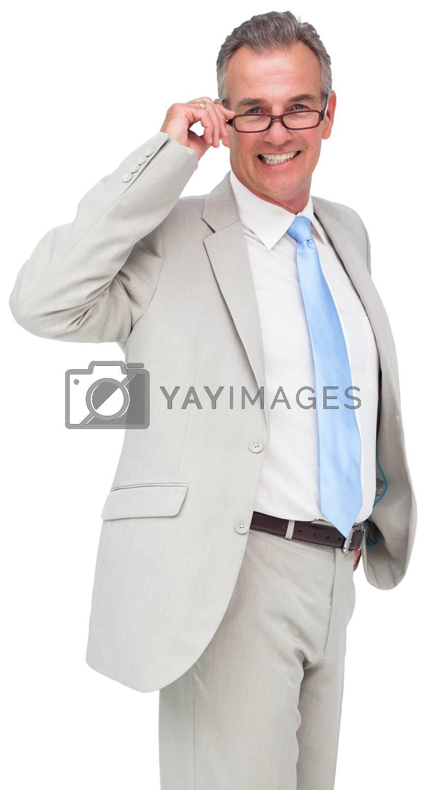 Royalty free image of Thinking mature businessman touching glasses by Wavebreakmedia