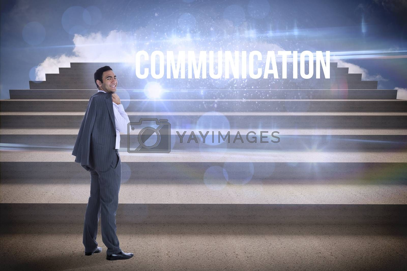 The word communication and smiling businessman standing against steps against blue sky
