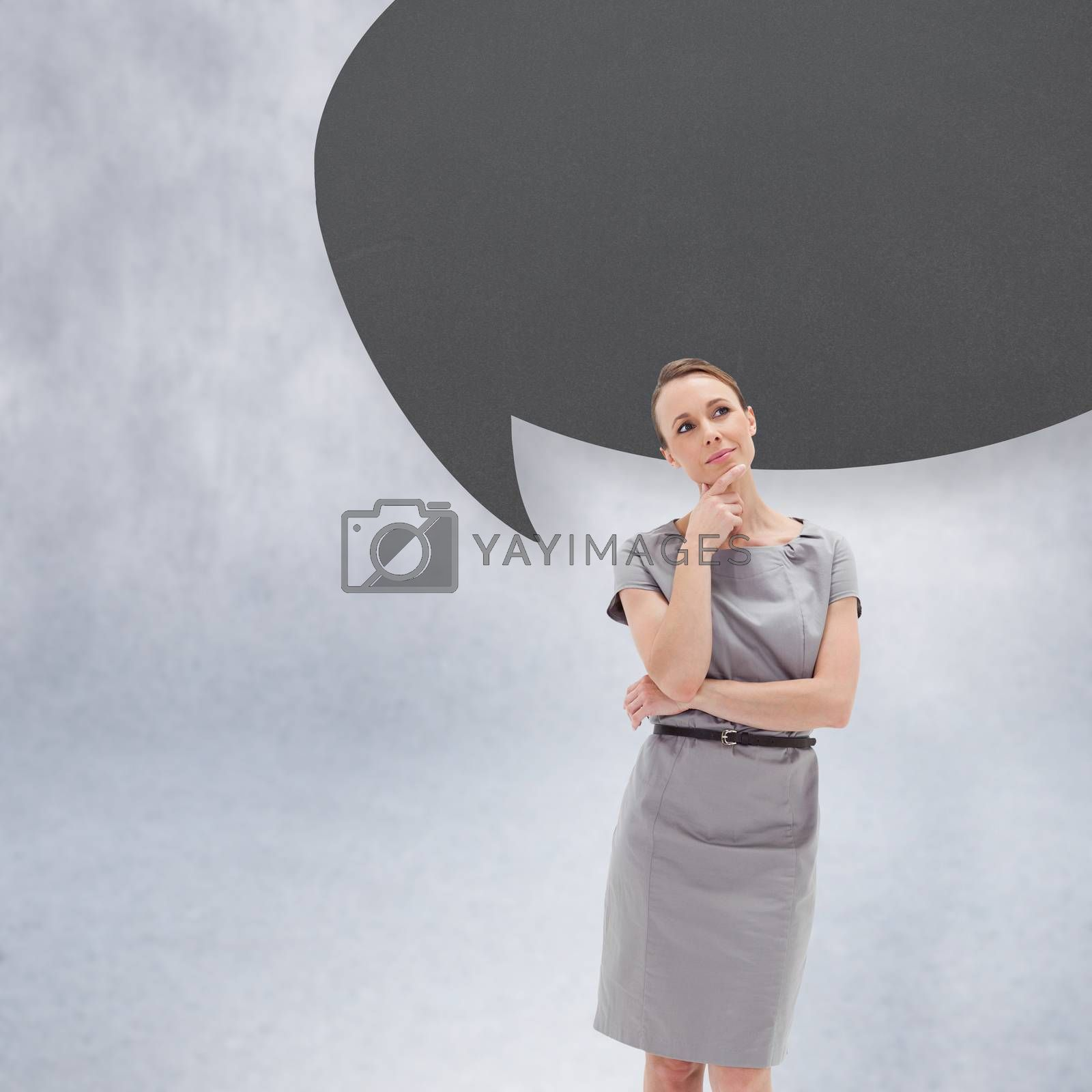Thoughtful woman posing in dress with speech bubble against grey wall