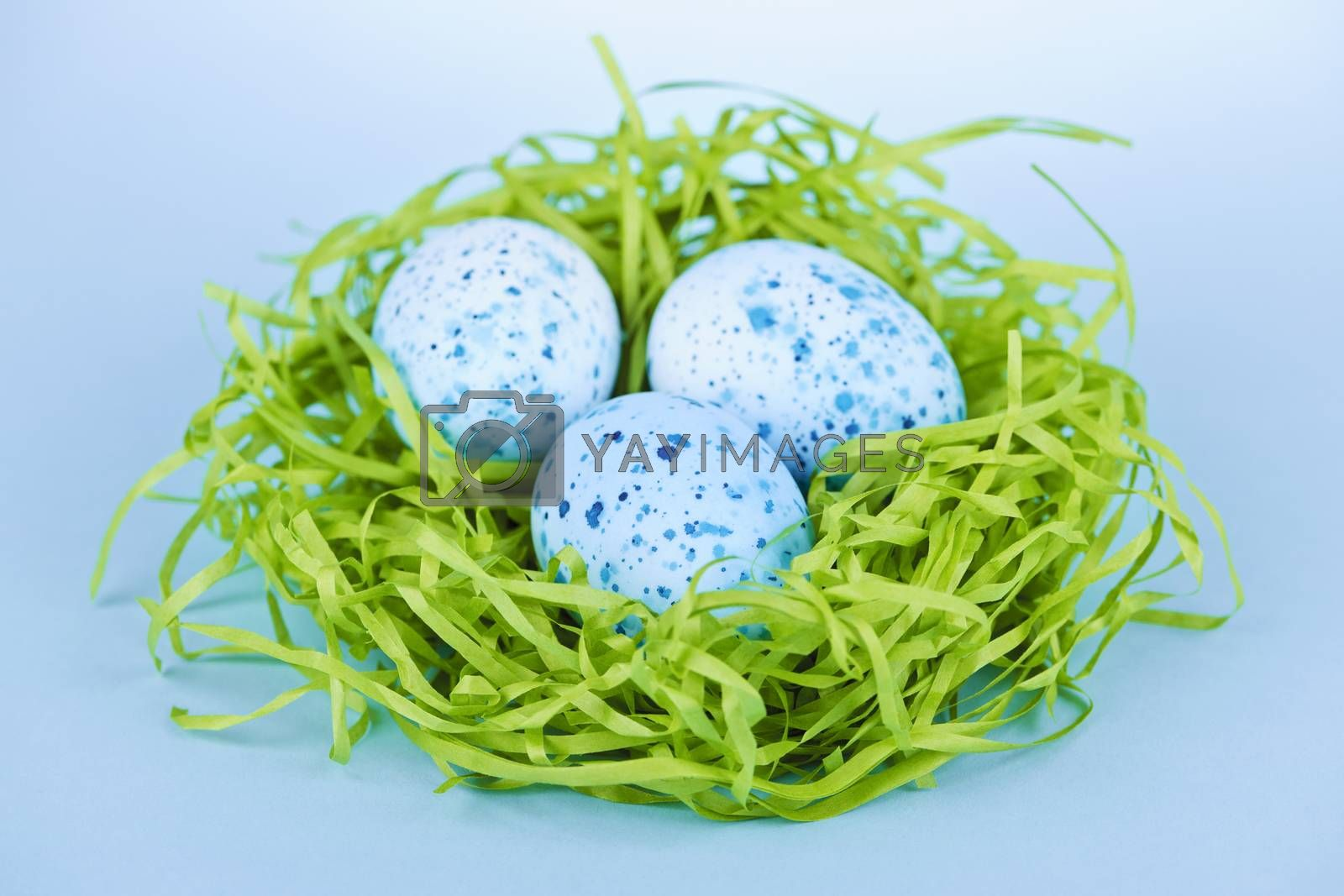 Three blue speckled easter eggs in green paper grass nest