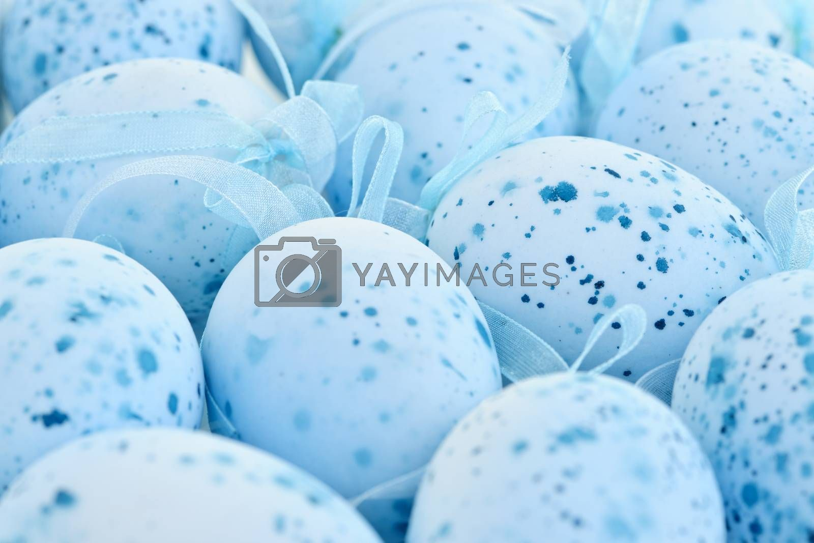 Pale blue speckled painted Easter eggs with ribbons