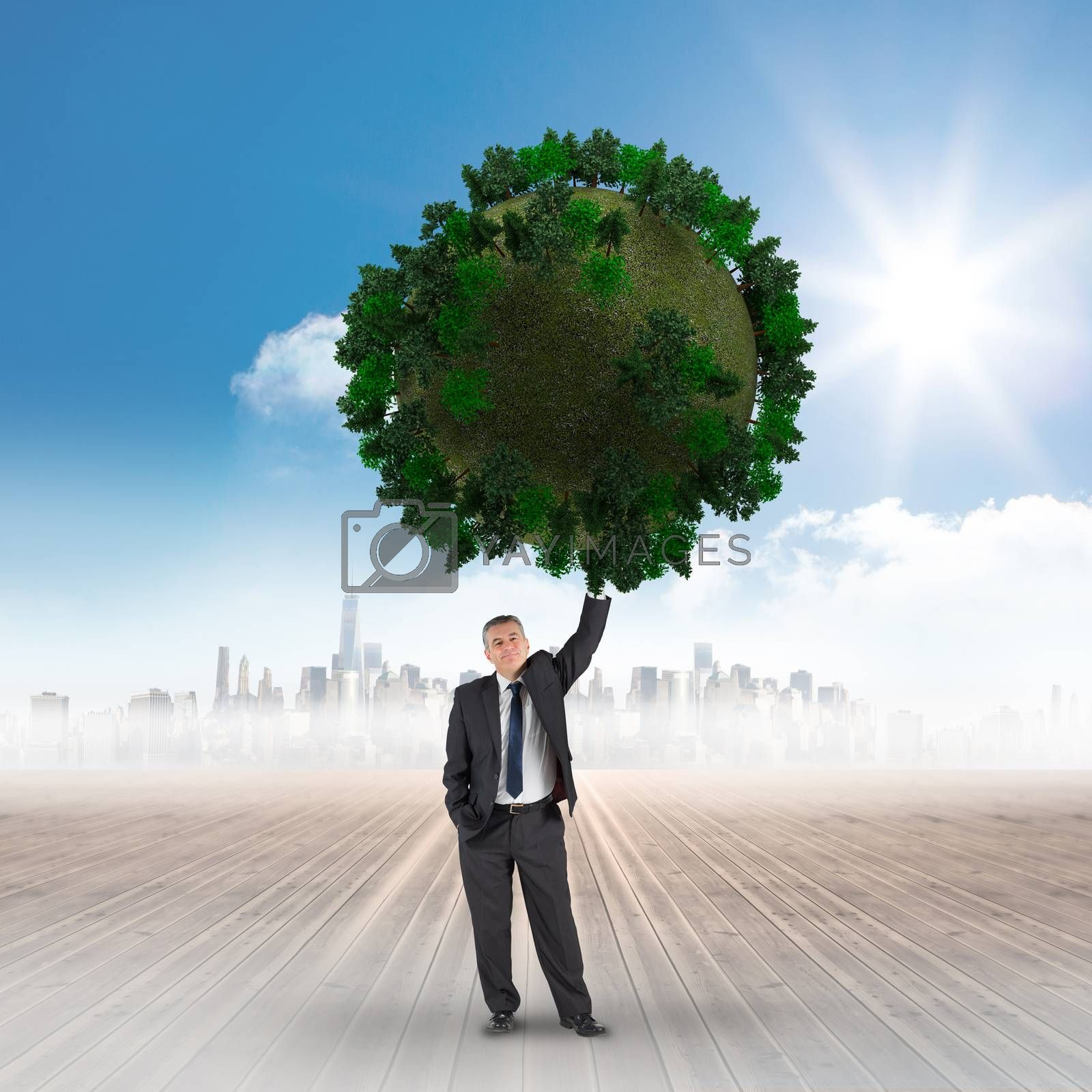 Composite image of businessman holding green sphere against cityscape on the horizon