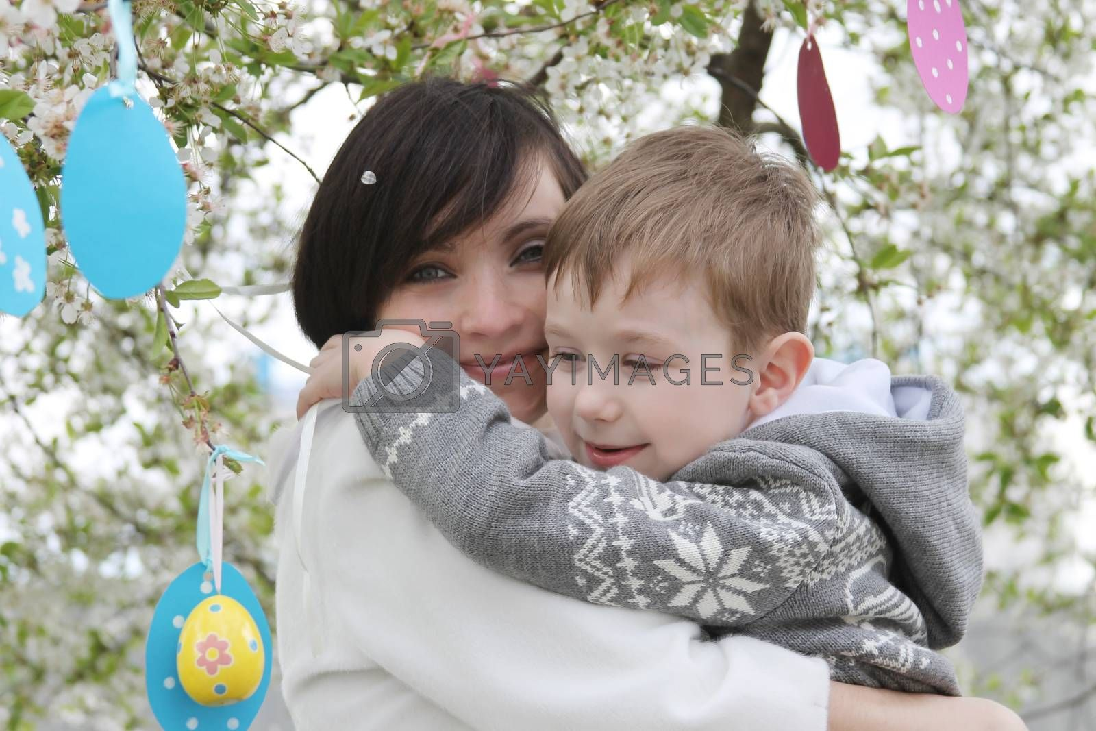Happy mother and son in blooming garden decorating for Easter