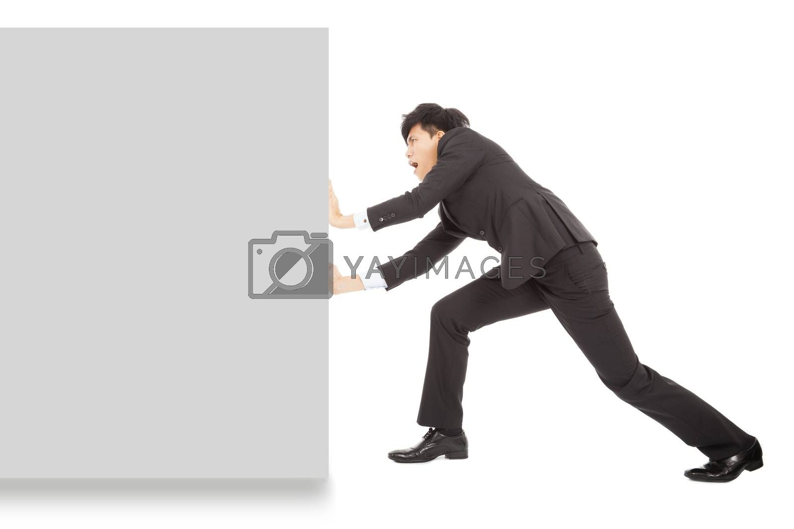 Royalty free image of Young businessman pushing a blank board on white background by tomwang