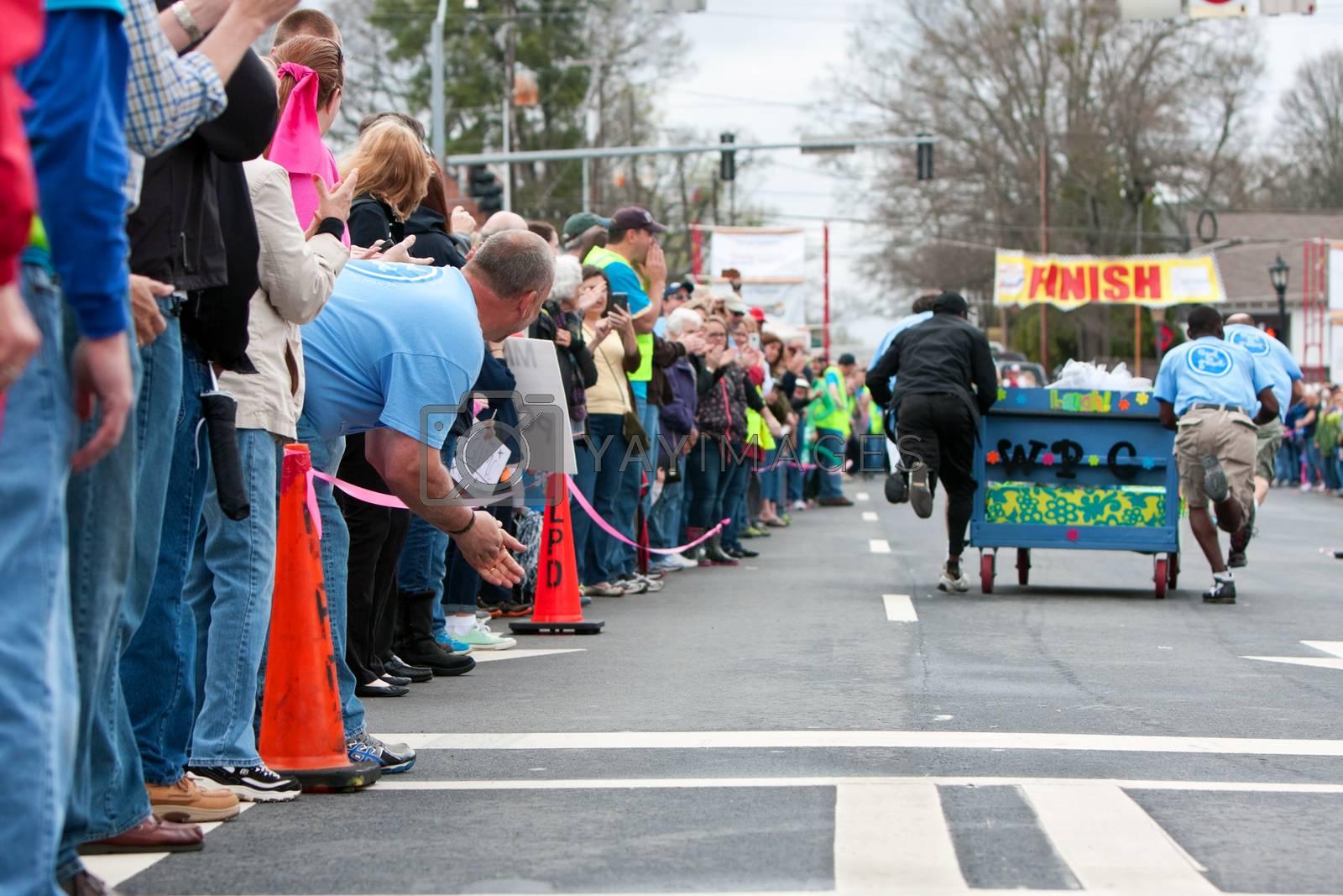 Royalty free image of Spectators Cheer Team Pushing Bed Toward Finish Of Fundraiser Ra by BluIz60
