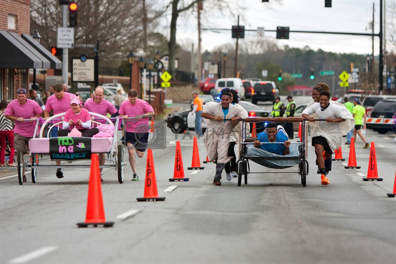 Royalty free image of Teams Push Silly Beds Down Street In Fundraiser Race by BluIz60