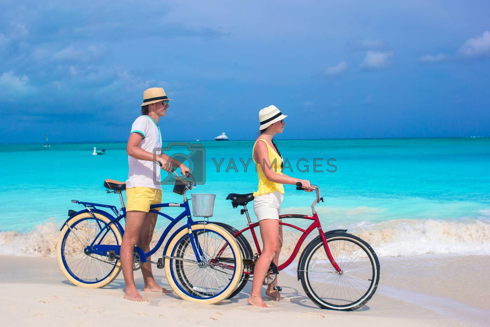 Royalty free image of Young happy couple riding bikes on white tropical beach by travnikovstudio