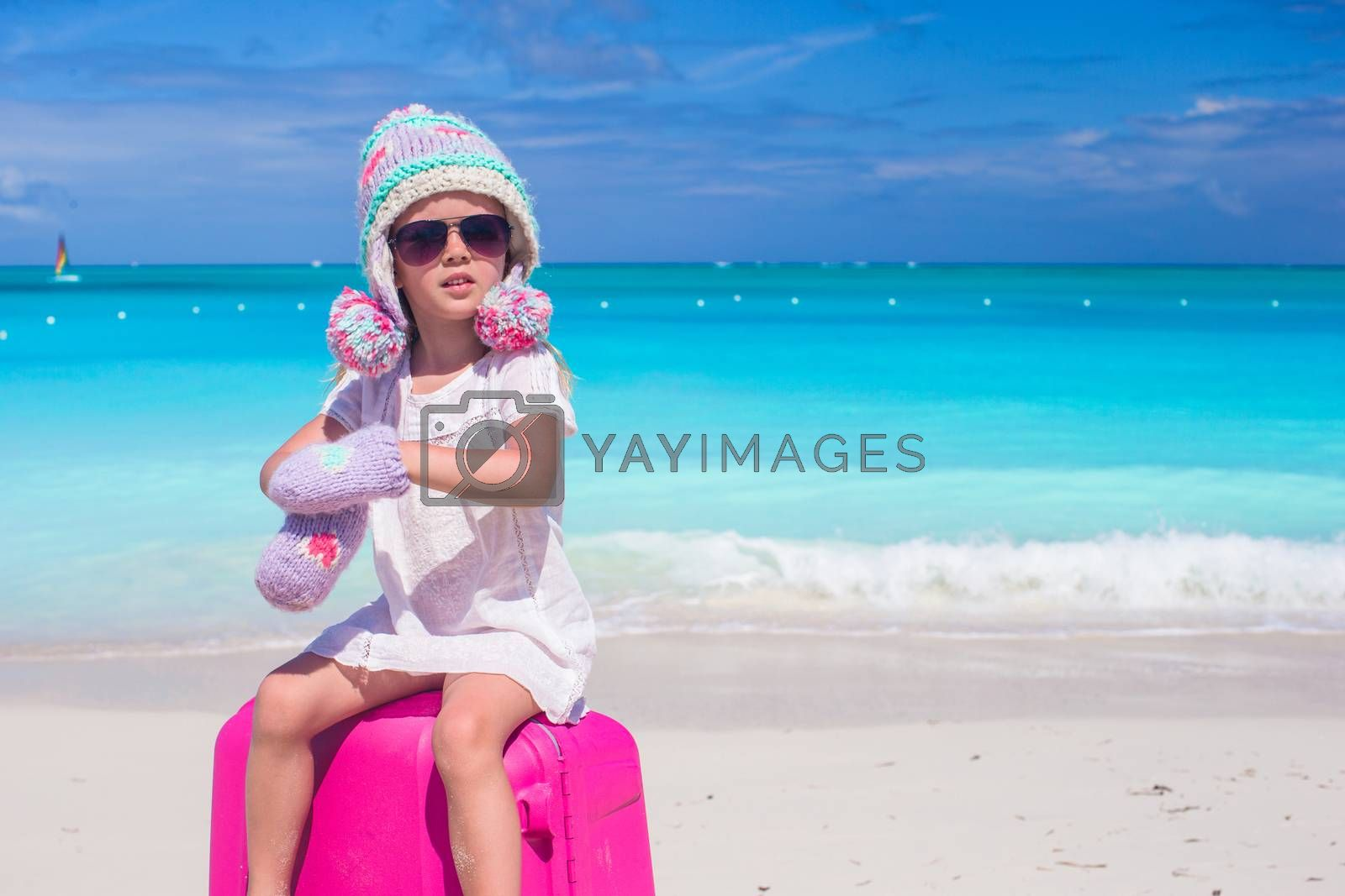 Royalty free image of Little adorable girl in winter hat and mittens on summer vacation by travnikovstudio