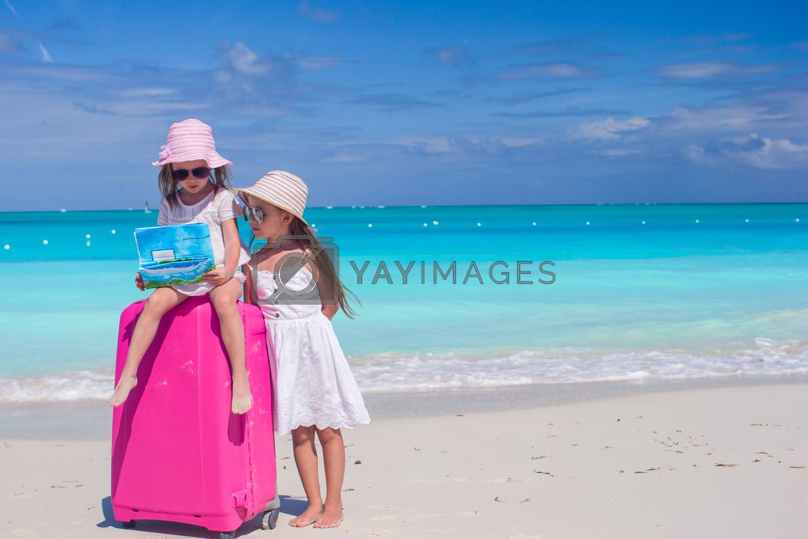 Royalty free image of Little girls with big suitcase and a map searching the way on tropical beach by travnikovstudio