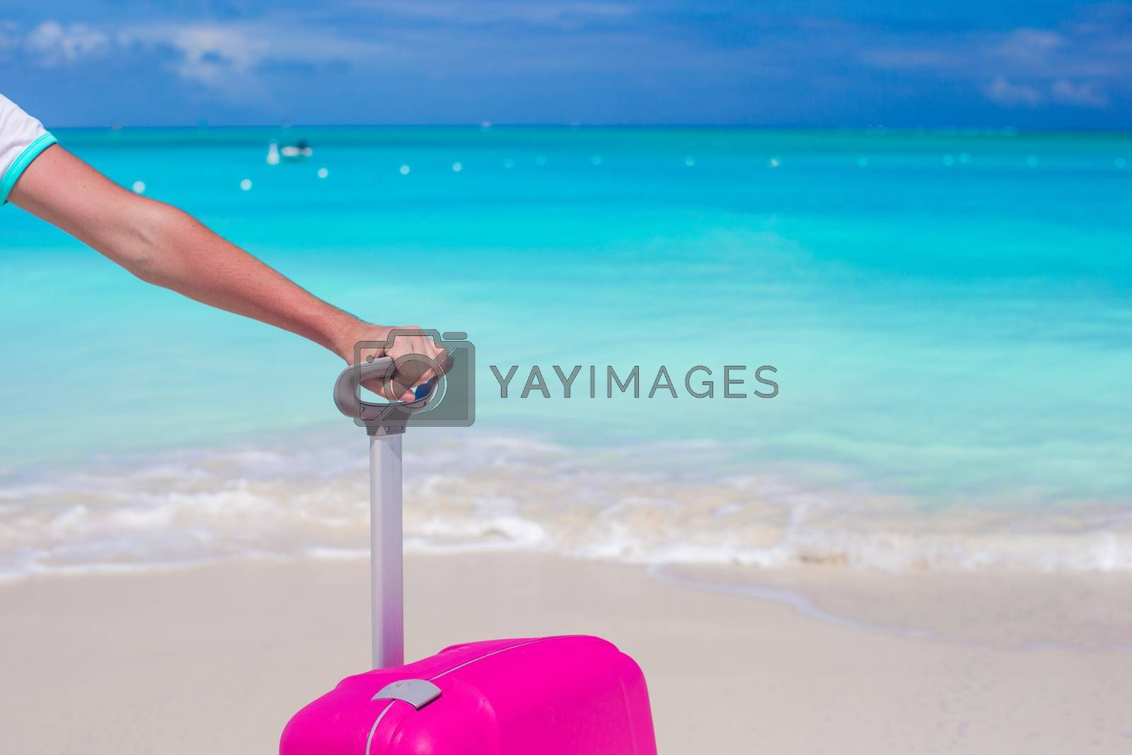 Royalty free image of Close up hand holding suitcase on tropical beach by travnikovstudio