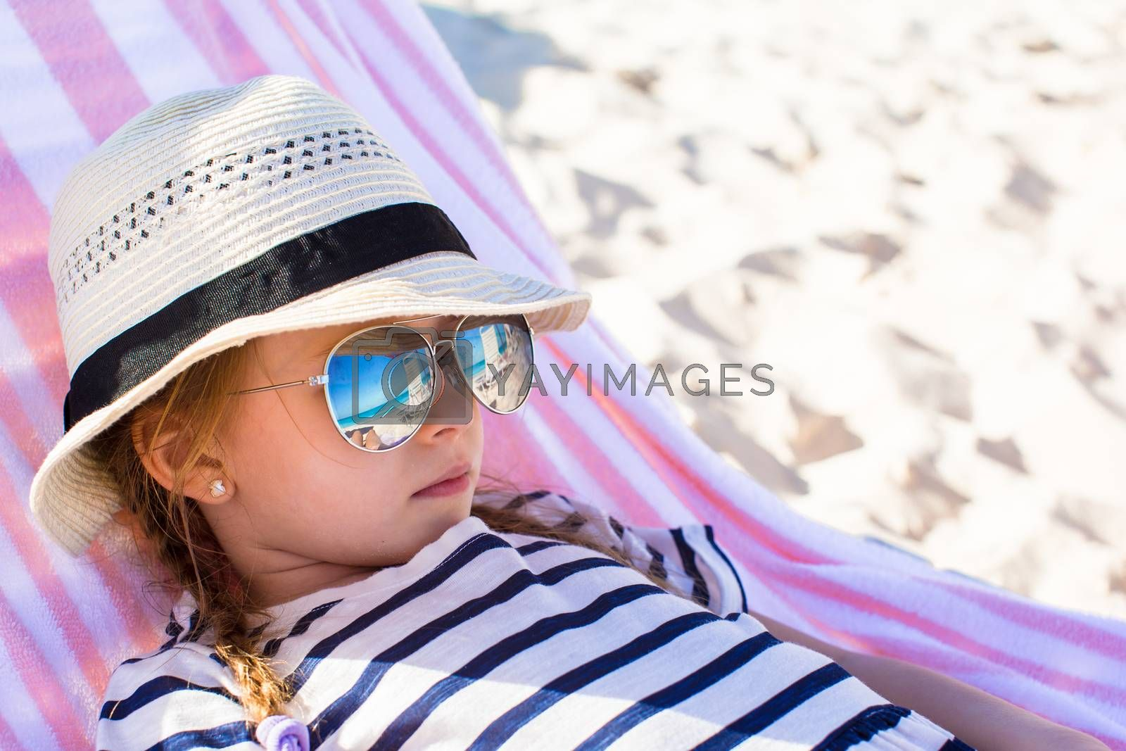 Royalty free image of Portrait of little adorable girl lying on beach lounger by travnikovstudio