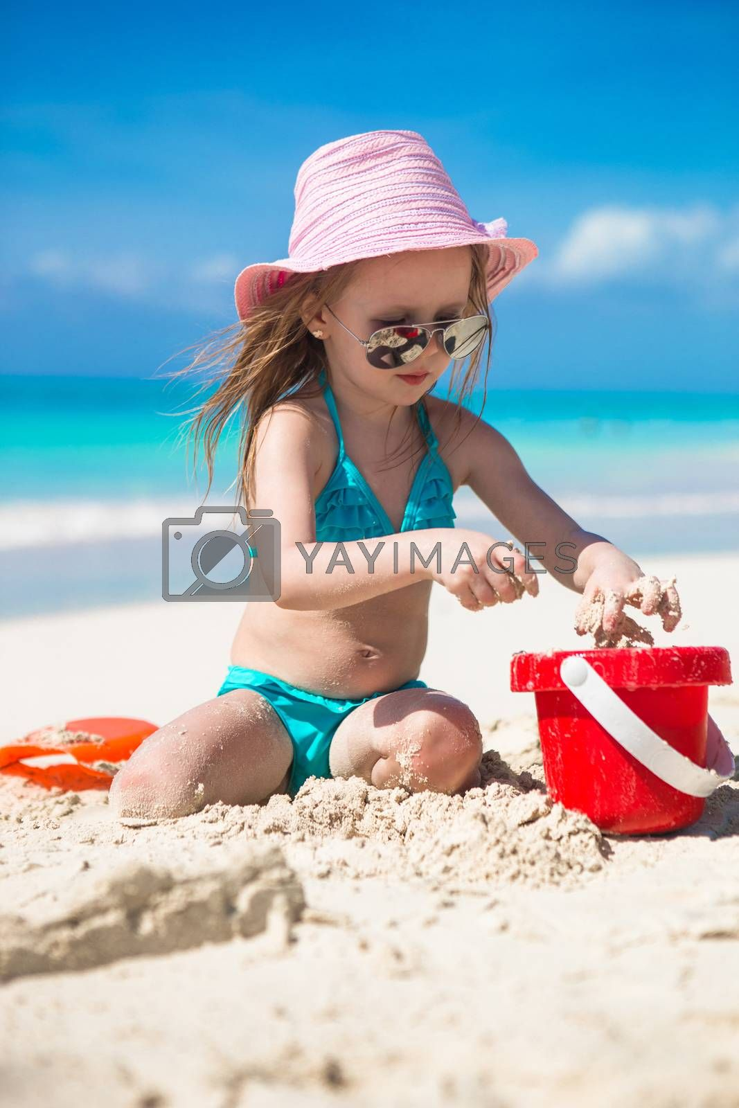 Royalty free image of Adorable little girl playing on the beach with white sand by travnikovstudio