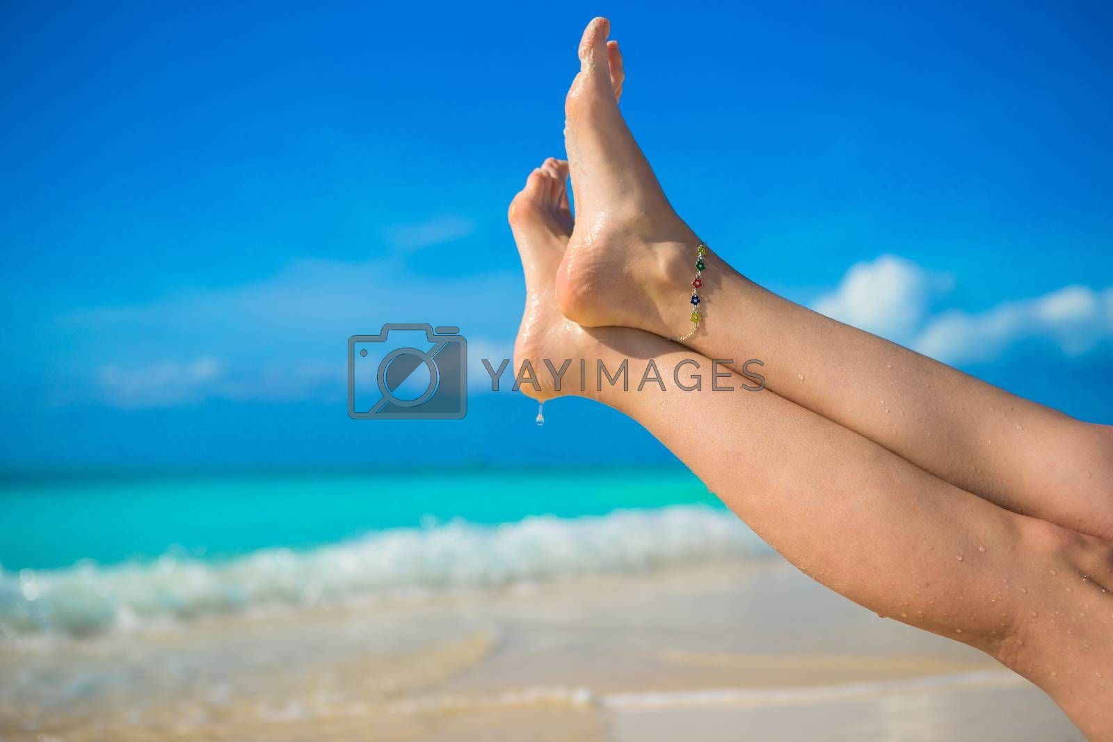 Royalty free image of Close up of female feet on white sandy beach by travnikovstudio