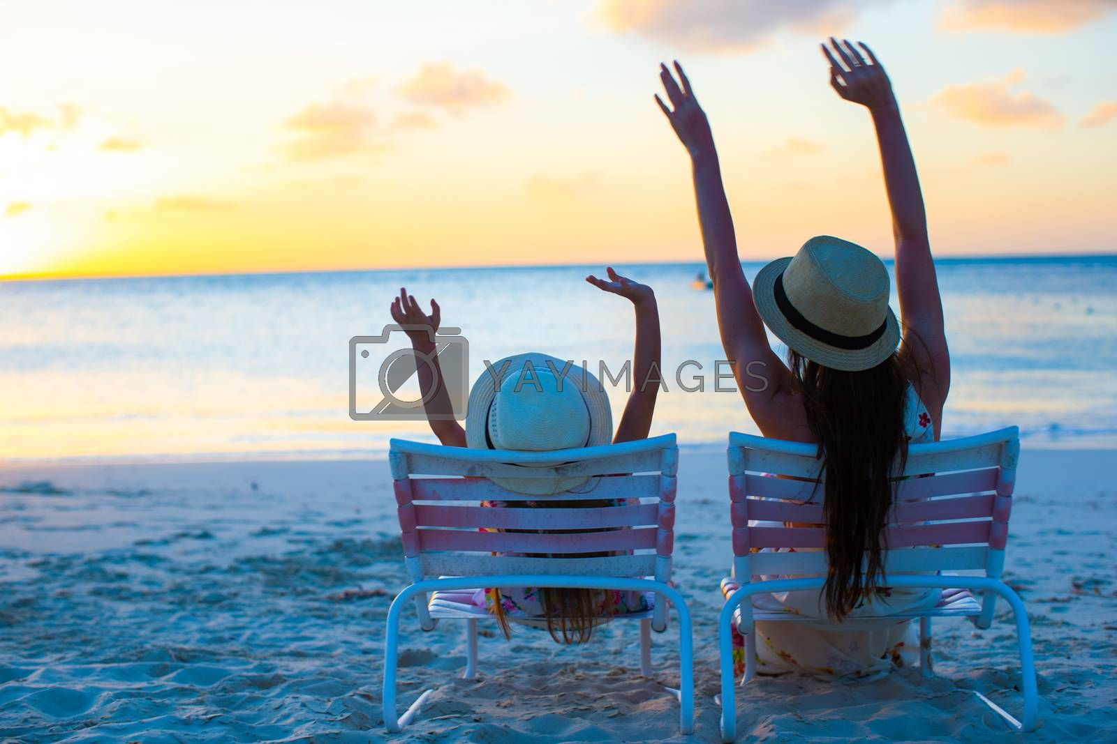 Royalty free image of Little girl and mother sitting on beach chairs at sunset by travnikovstudio
