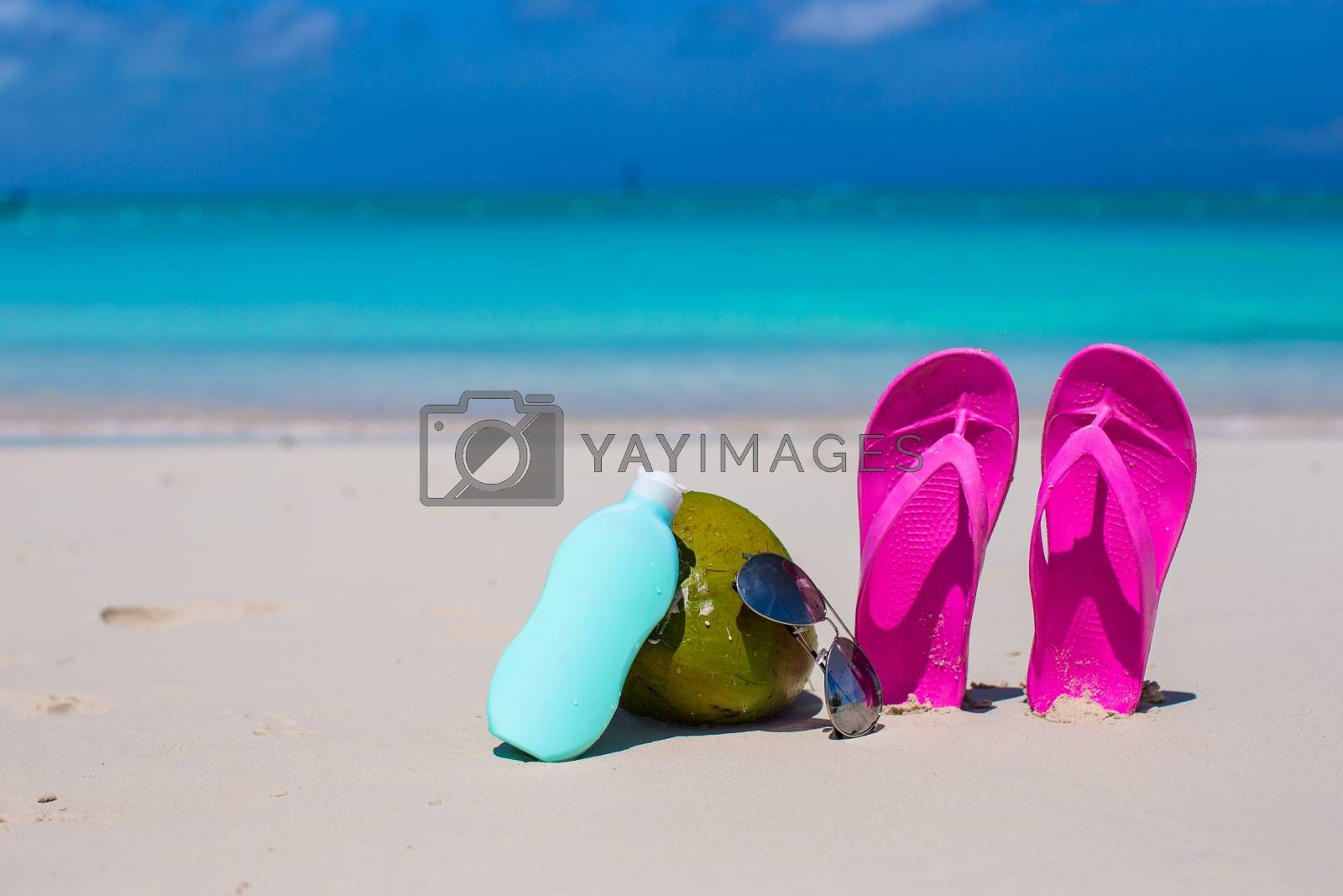 Royalty free image of Flip flops, coconut and suncream on white sand by travnikovstudio