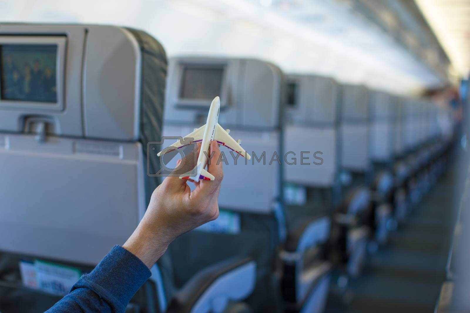 Close up hand holding an airplane model inside a aircraft