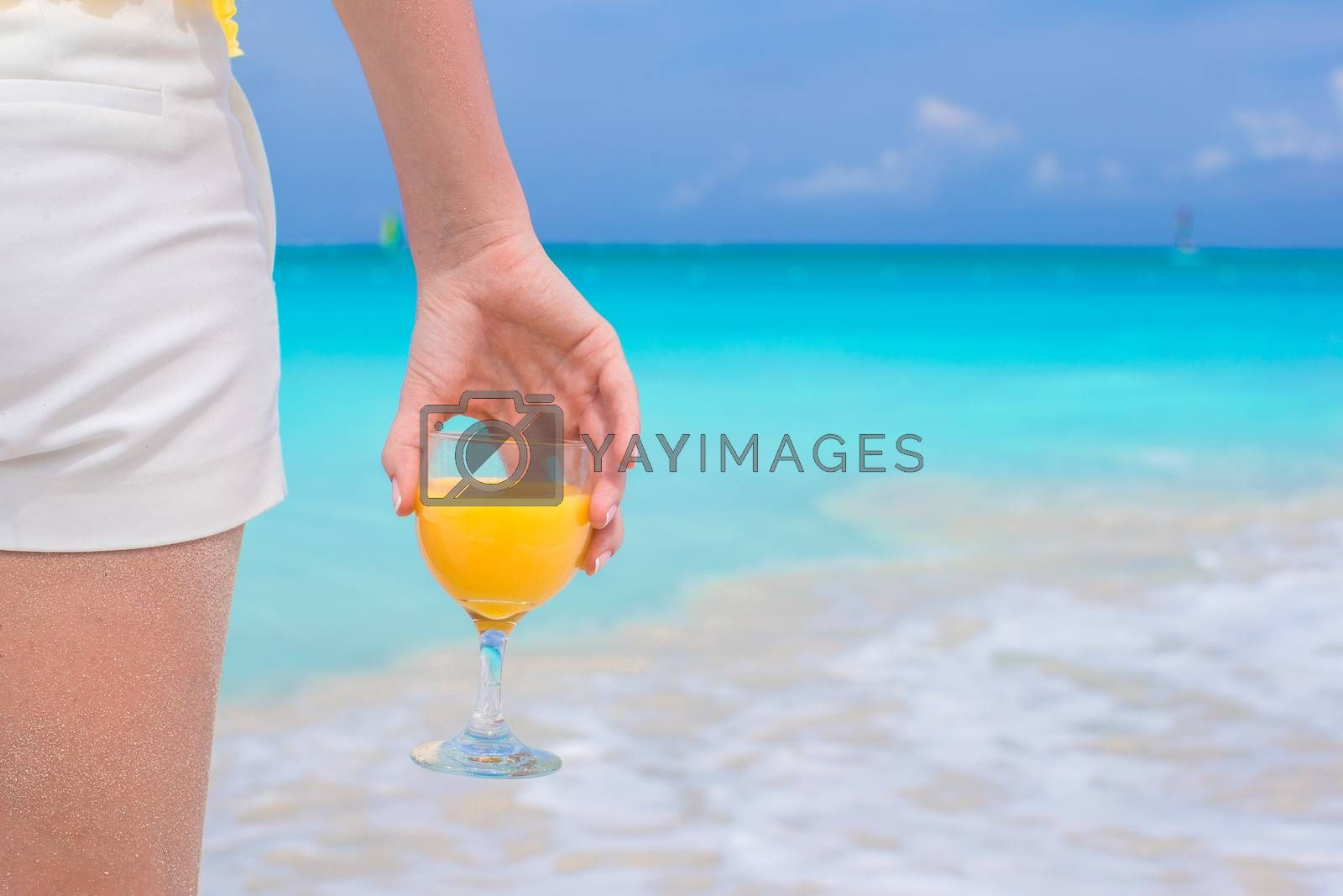 Royalty free image of Closeup orange juice in a female hand on background of the sea by travnikovstudio