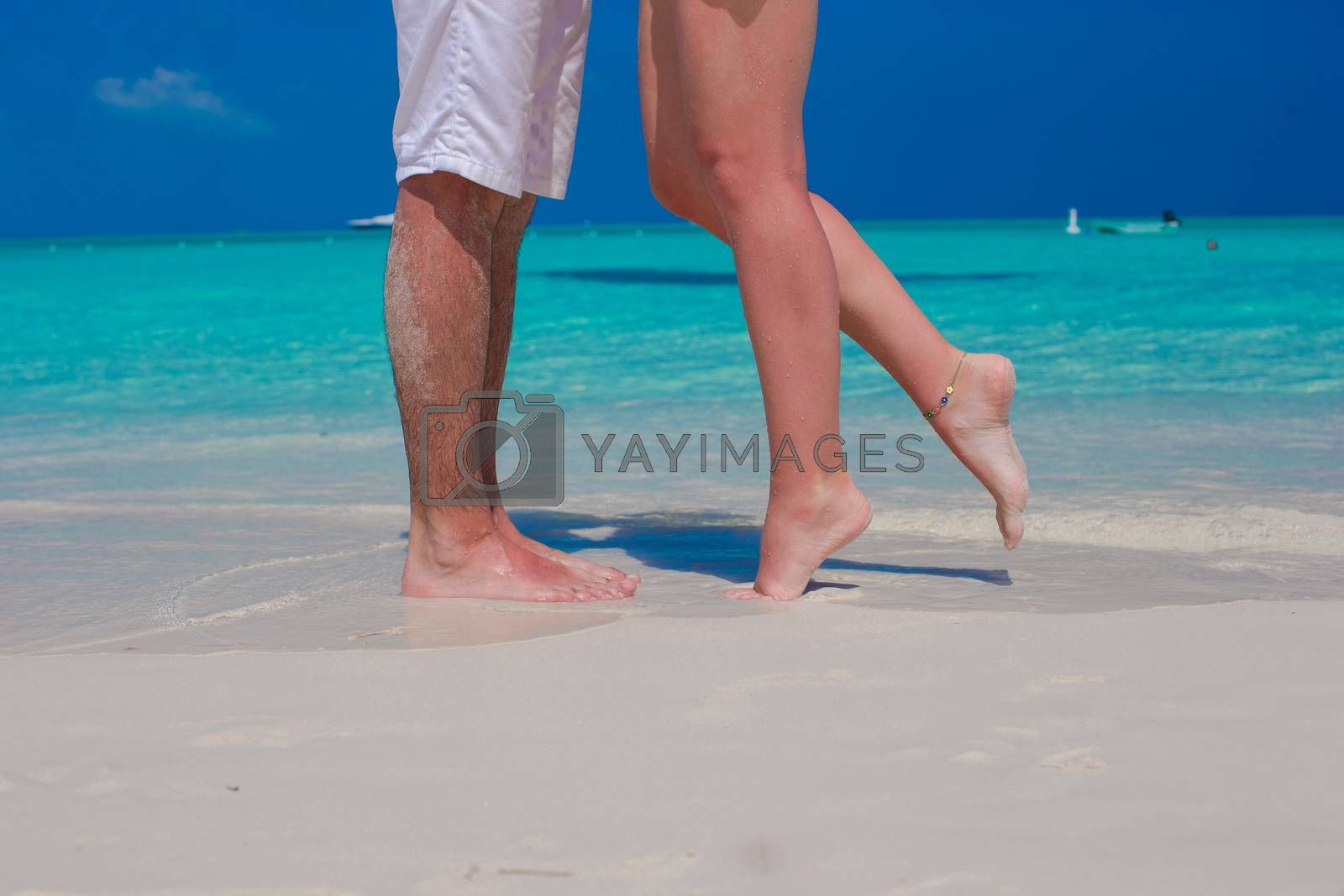 Royalty free image of Close up male and female feet on white sand by travnikovstudio