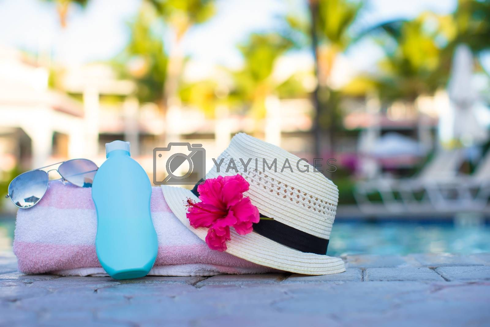 Royalty free image of Suncream, hat, sunglasses, flower and tower near swimming pool by travnikovstudio
