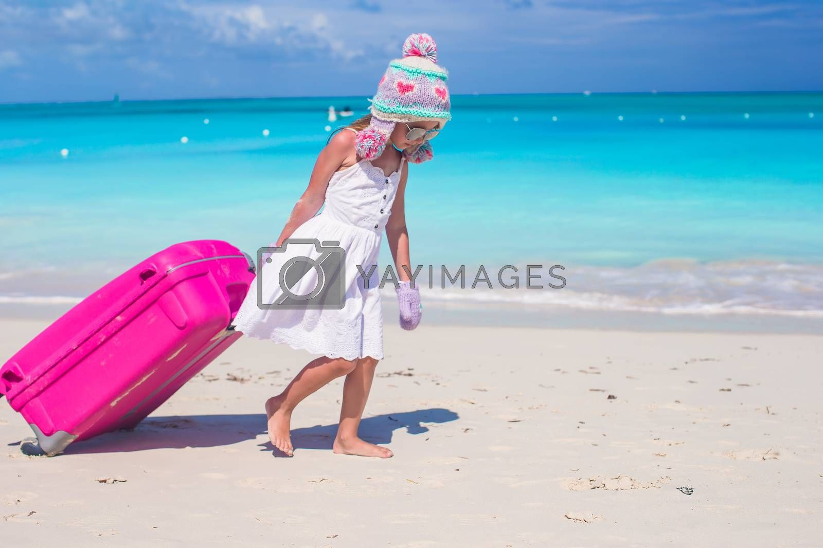 Royalty free image of Adorable girl in winter hat and mittens walking with luggage on beach by travnikovstudio