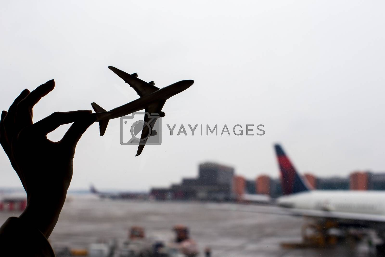 Royalty free image of Silhouette of a small airplane model on airport background by travnikovstudio