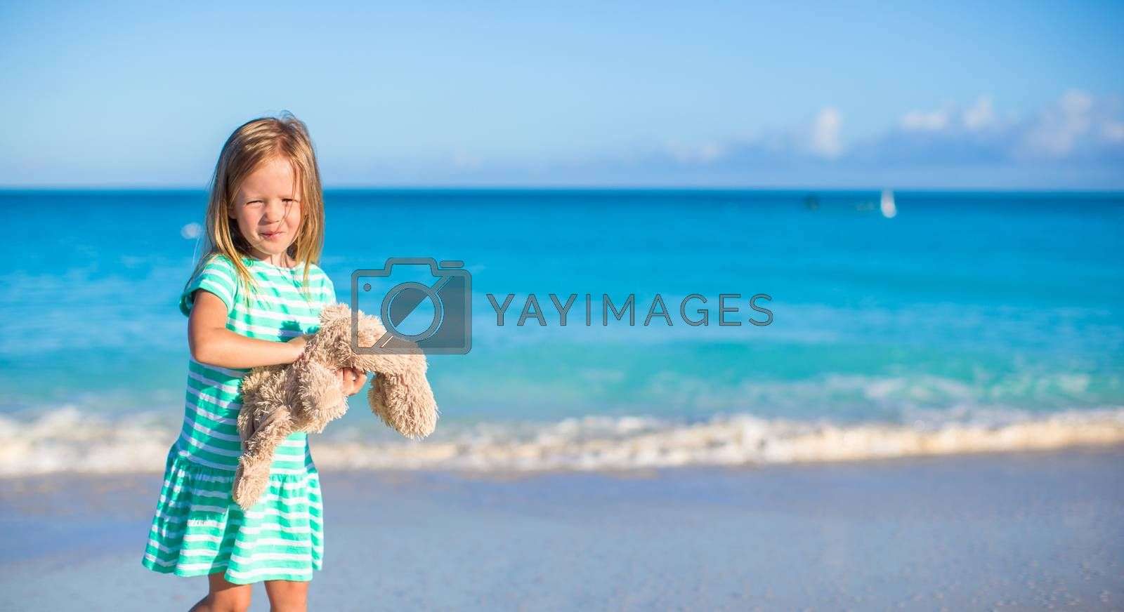 Royalty free image of Adorable little girl with her bunny toy on tropical beach vacation by travnikovstudio