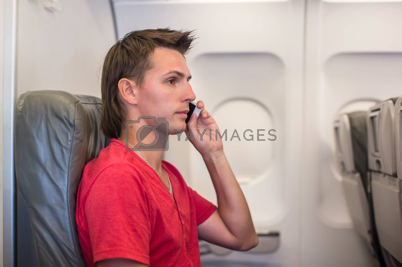 Young man talking the phone inside the aircraft while flying