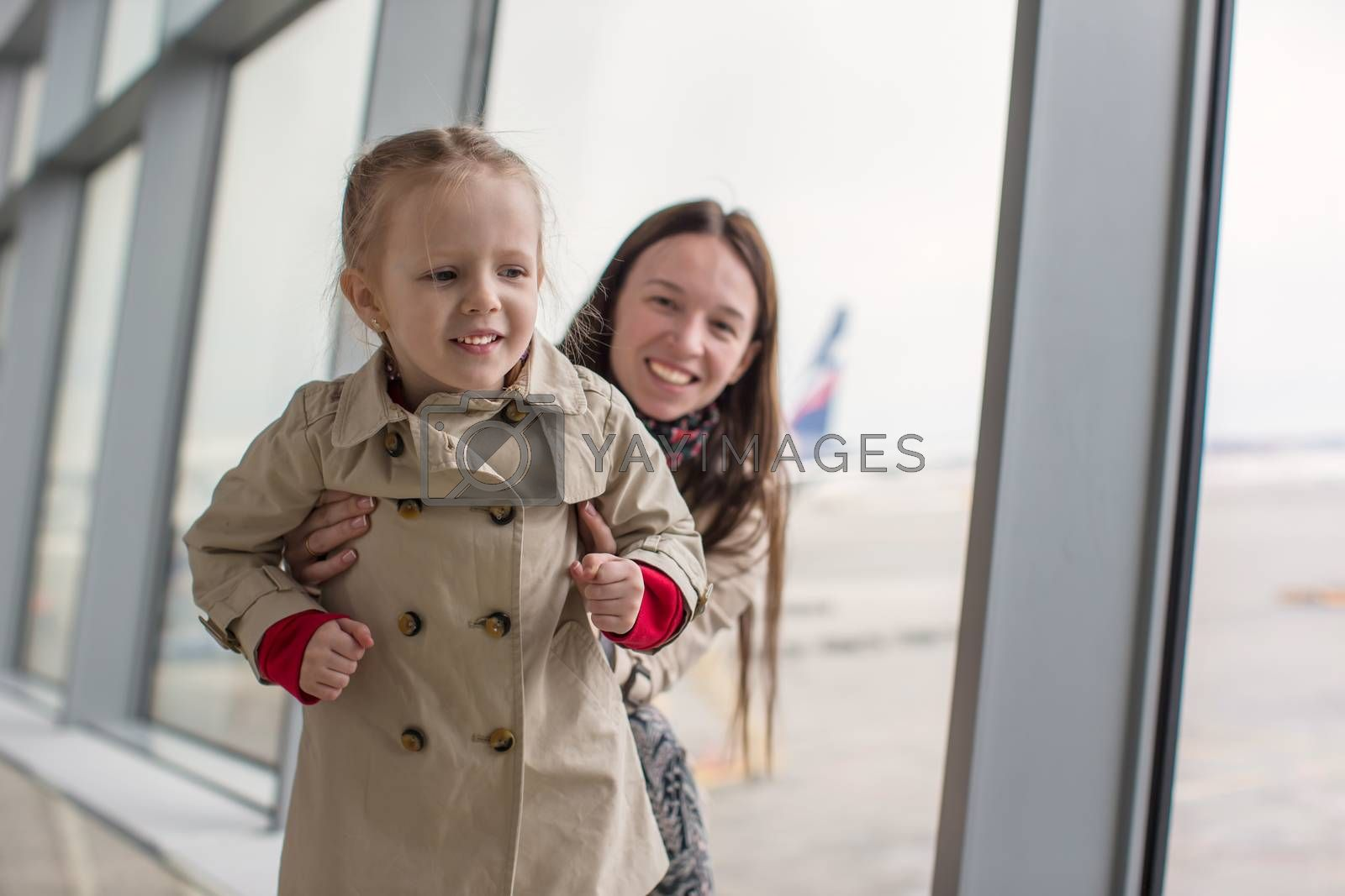 Mother and little daughter looking out the window at the airport terminal
