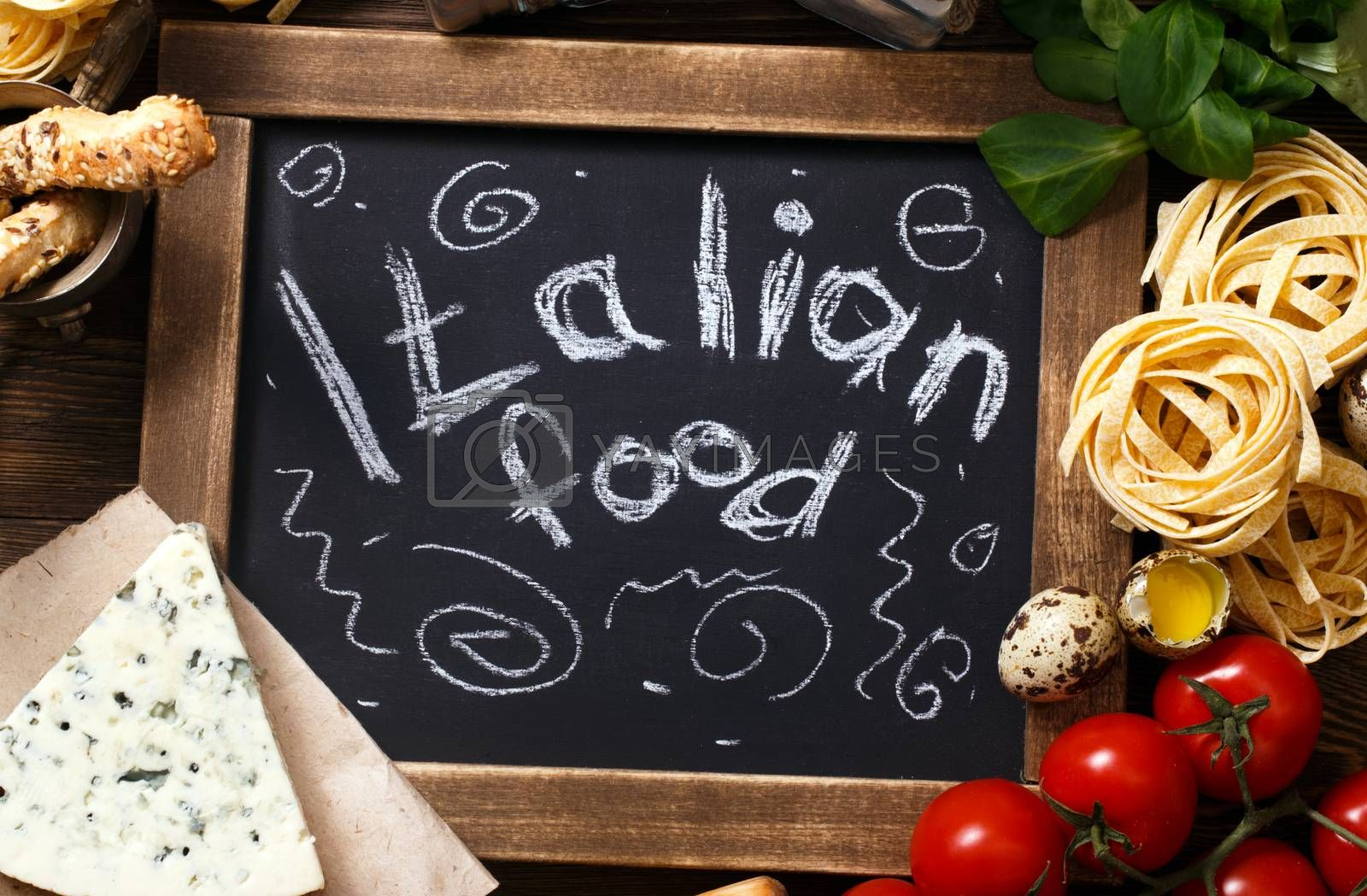 Royalty free image of Italian food on vintage wood background with chalkboard by primopiano