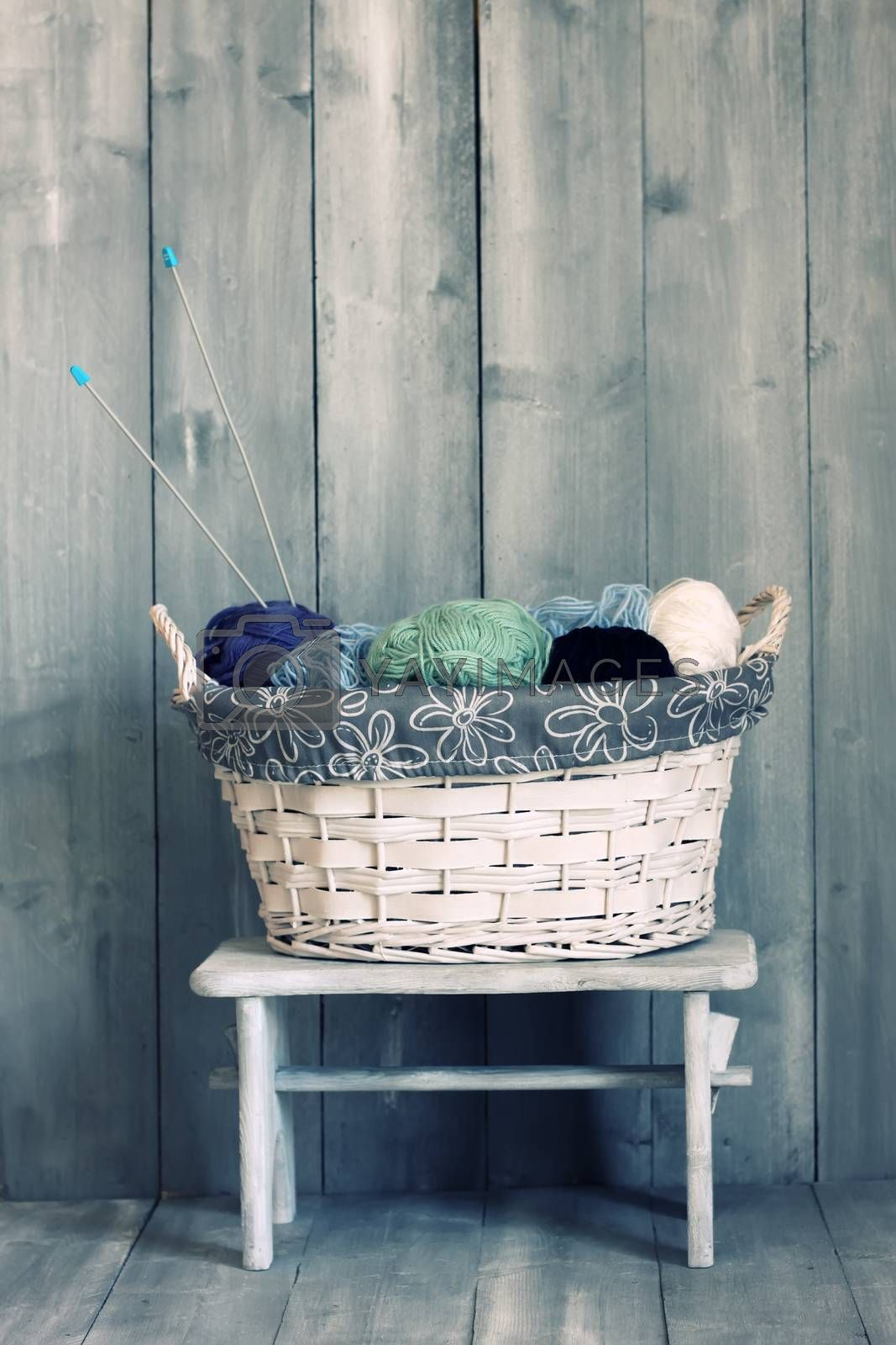 Photo of white basket with balls of wool